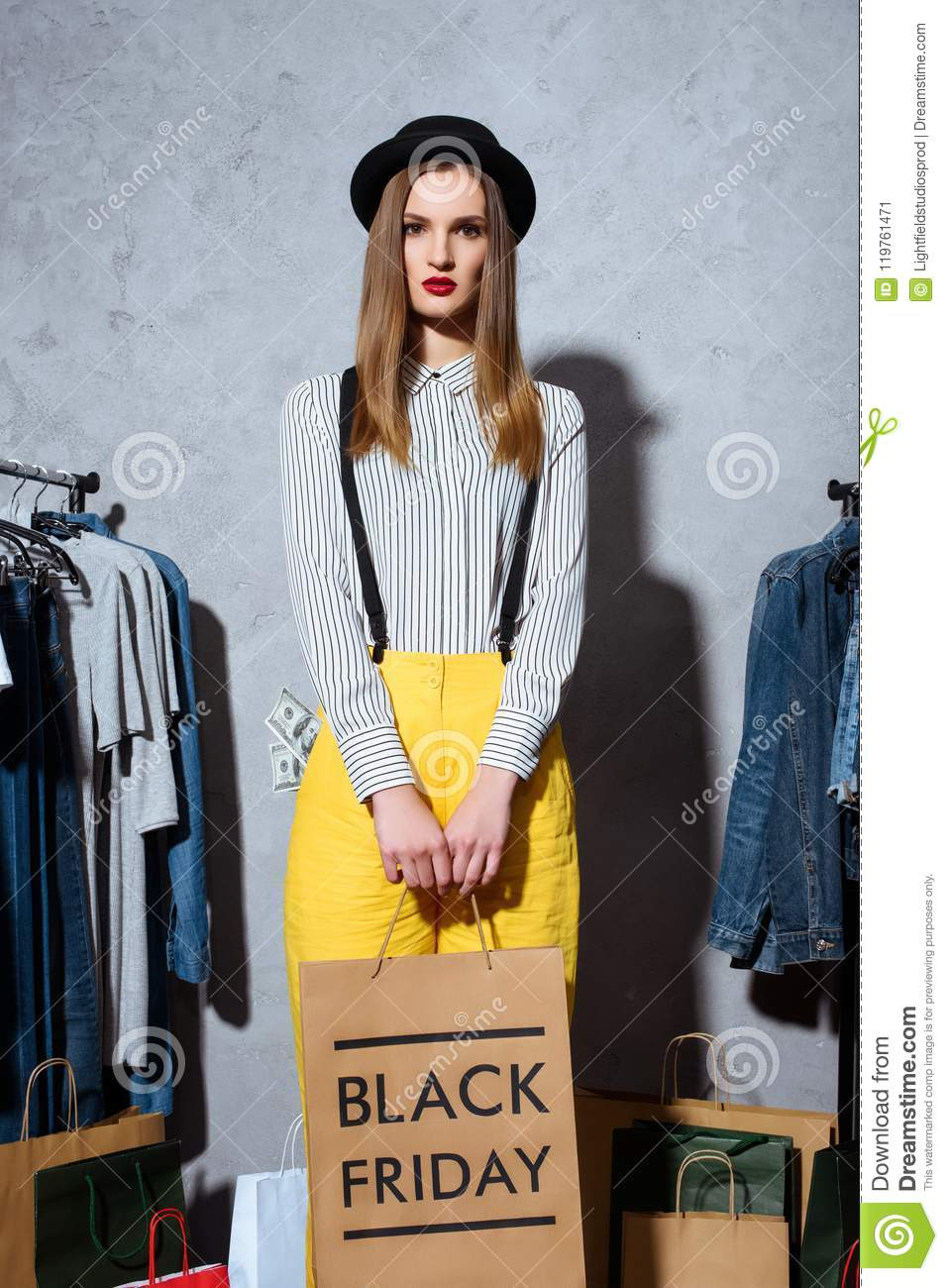 trendy girl with shopping bags and clothes around, black