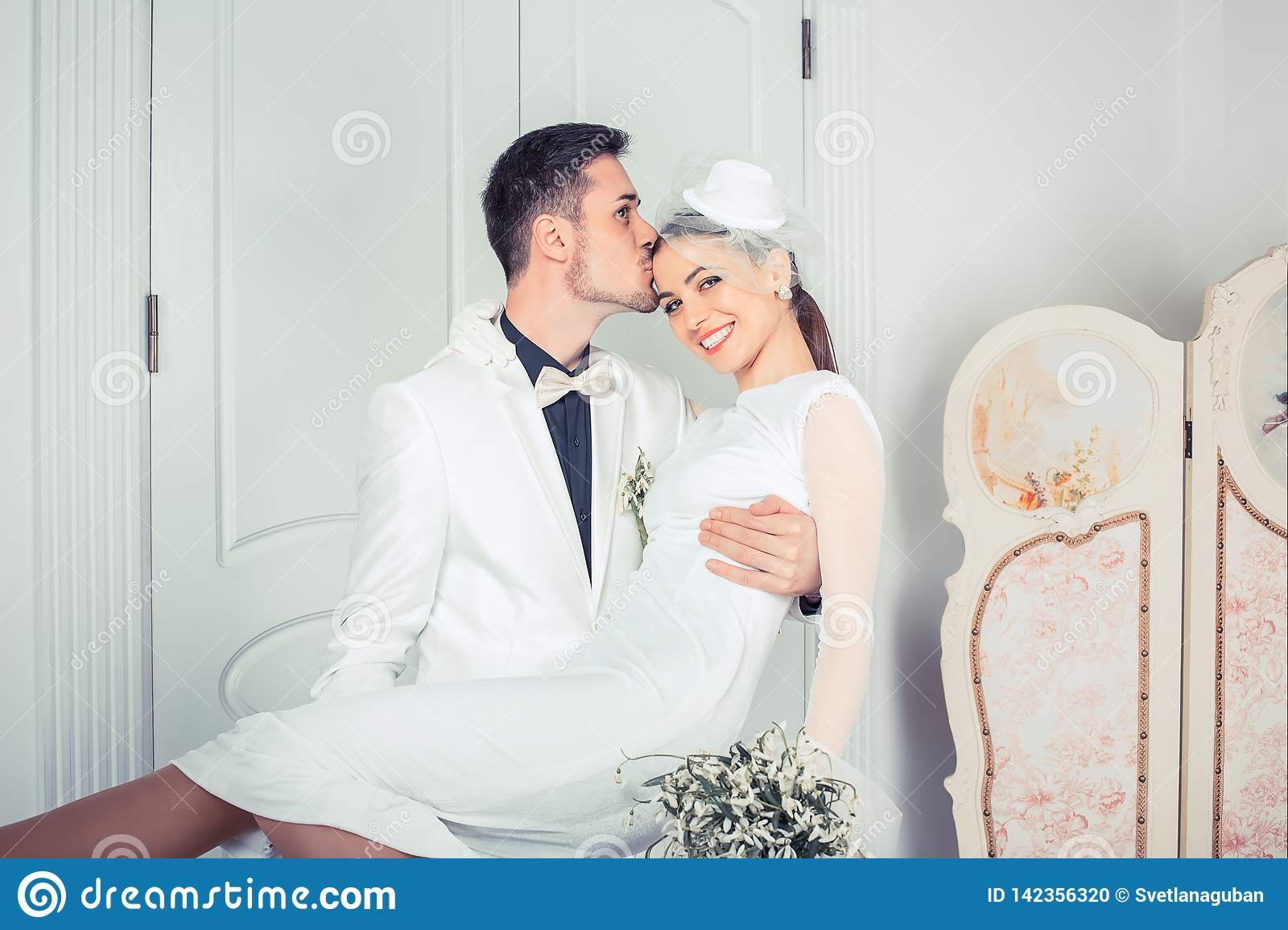 Loving groom holding woman on hands