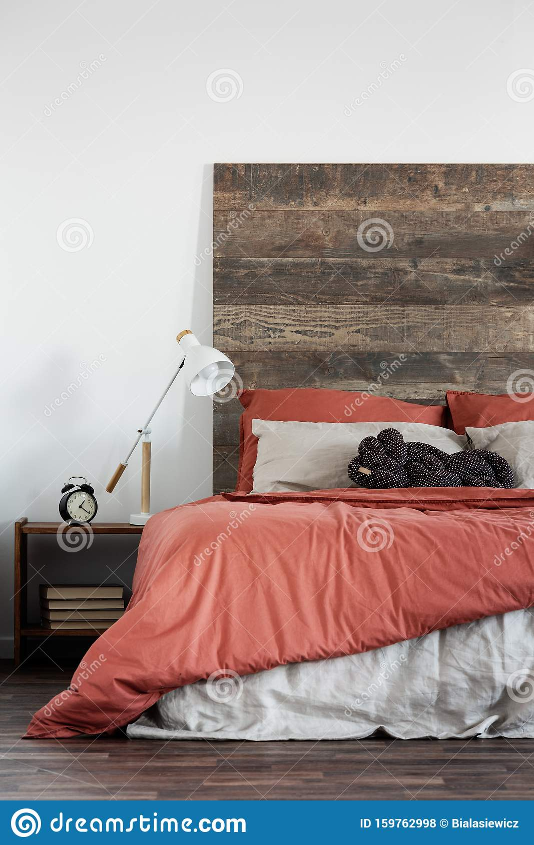Trendy White Lamp Next To Black Clock On Wooden Nightstand Next To King Size Bed With Wooden Headboard Stock Photo Image Of Headboard Bedside 159762998