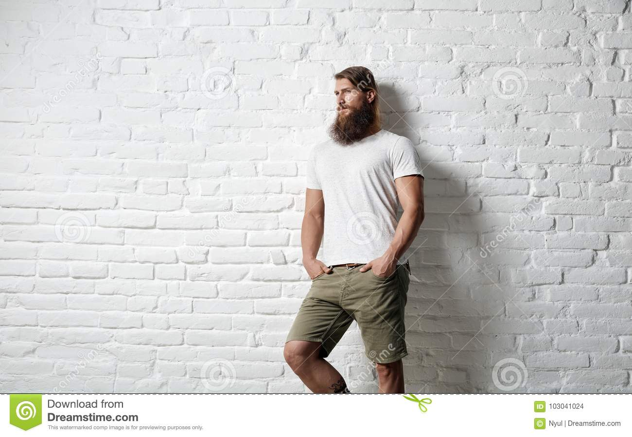 Trendy young bearded man against white brick wall