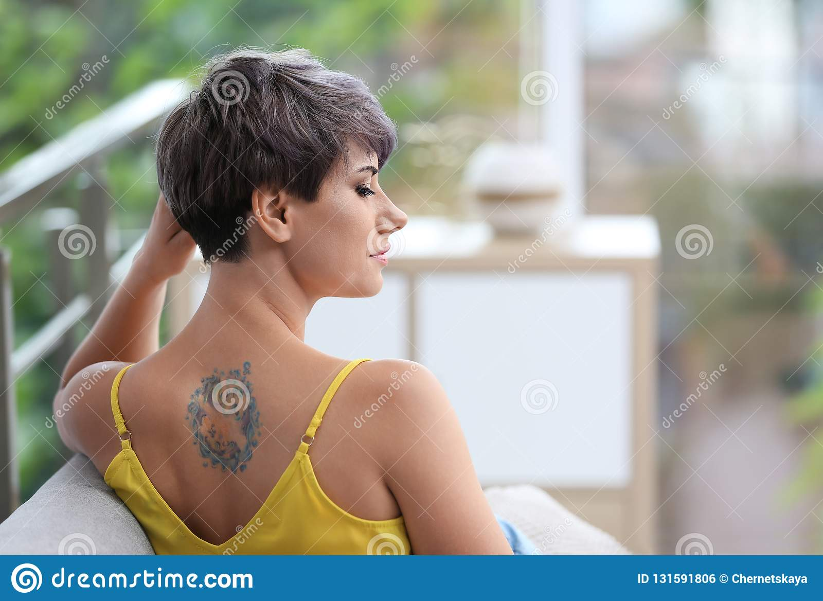 Trendy young woman with tattoo on sofa