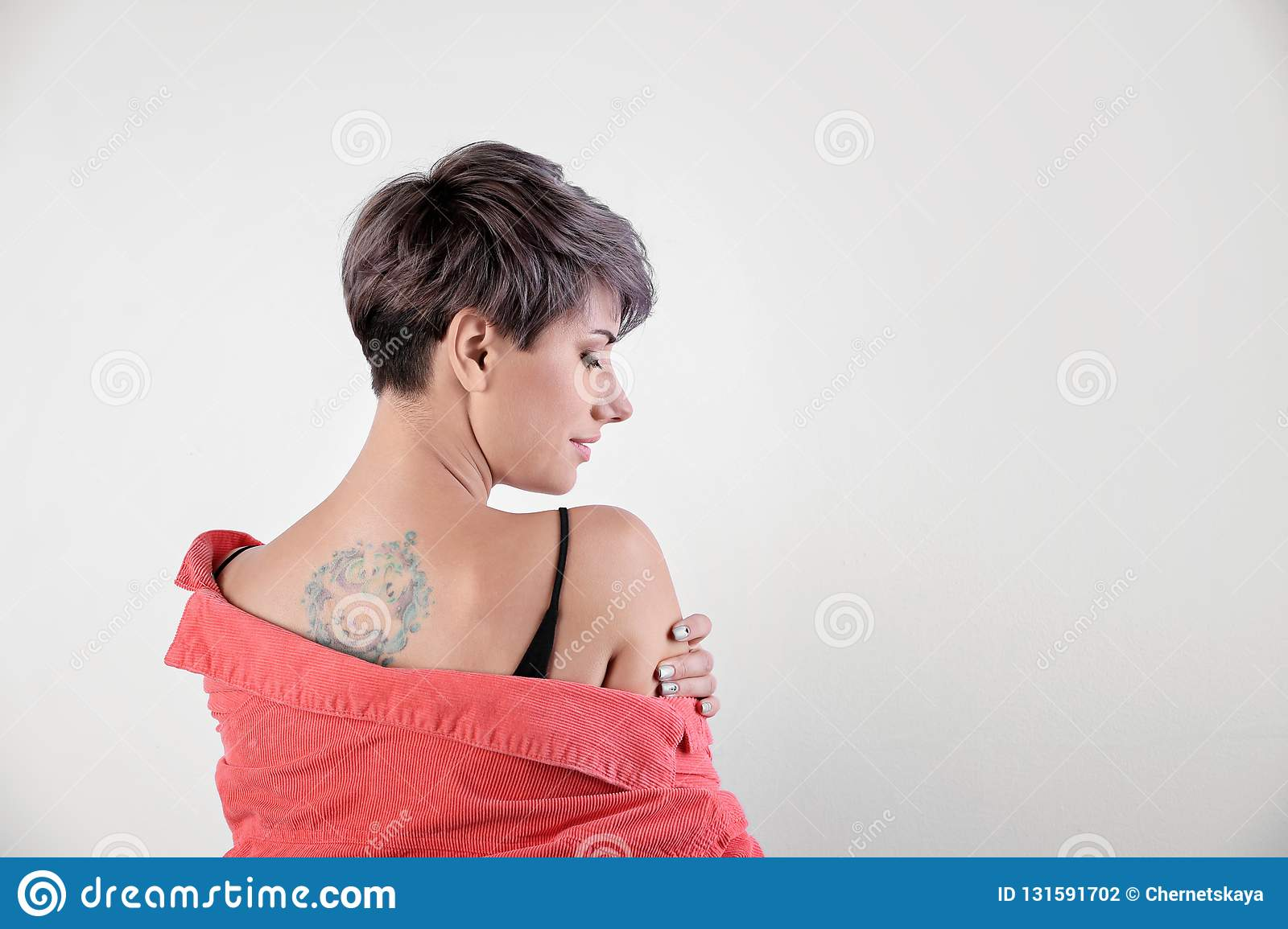 Trendy young woman with tattoo on white background.