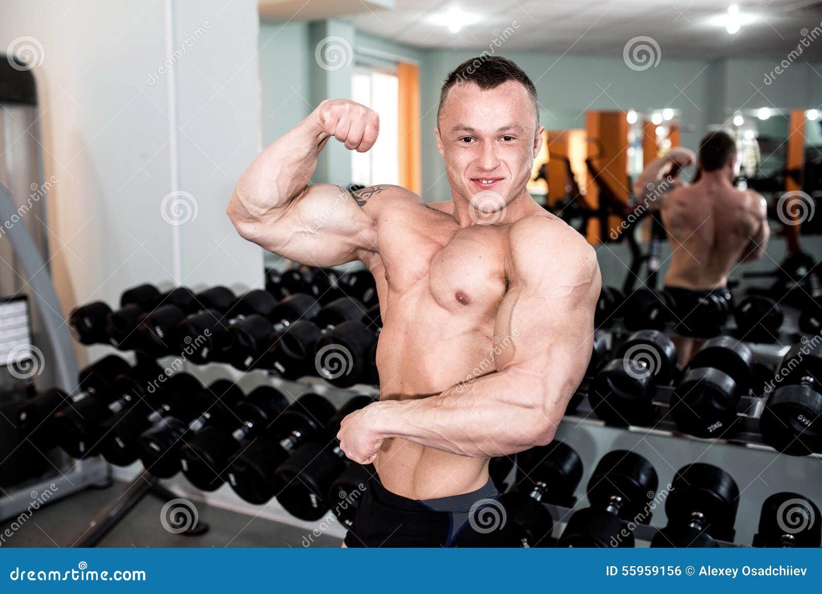 Trenes potentes del hombre en el gimnasio