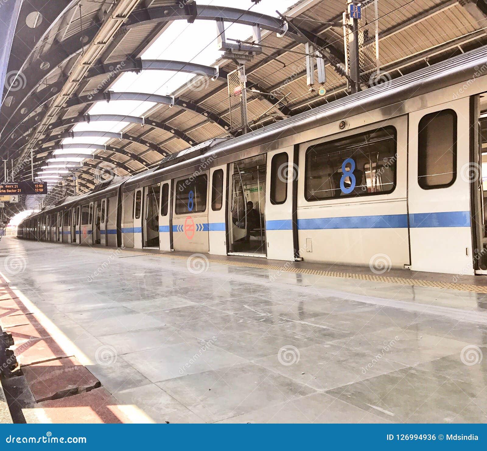 Treno della metropolitana di Delhi ad una stazione della metropolitana più di meno ammucchiata a Nuova Delhi nel tempo di mezzogi