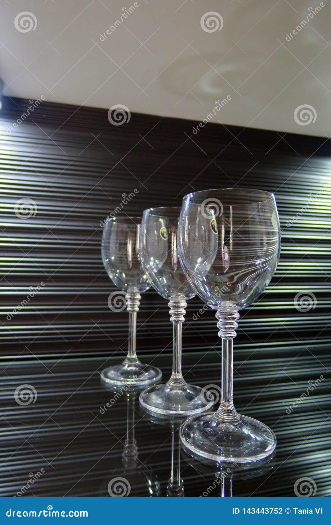 Tres altos vidrios transparentes en un fondo marrón hermoso