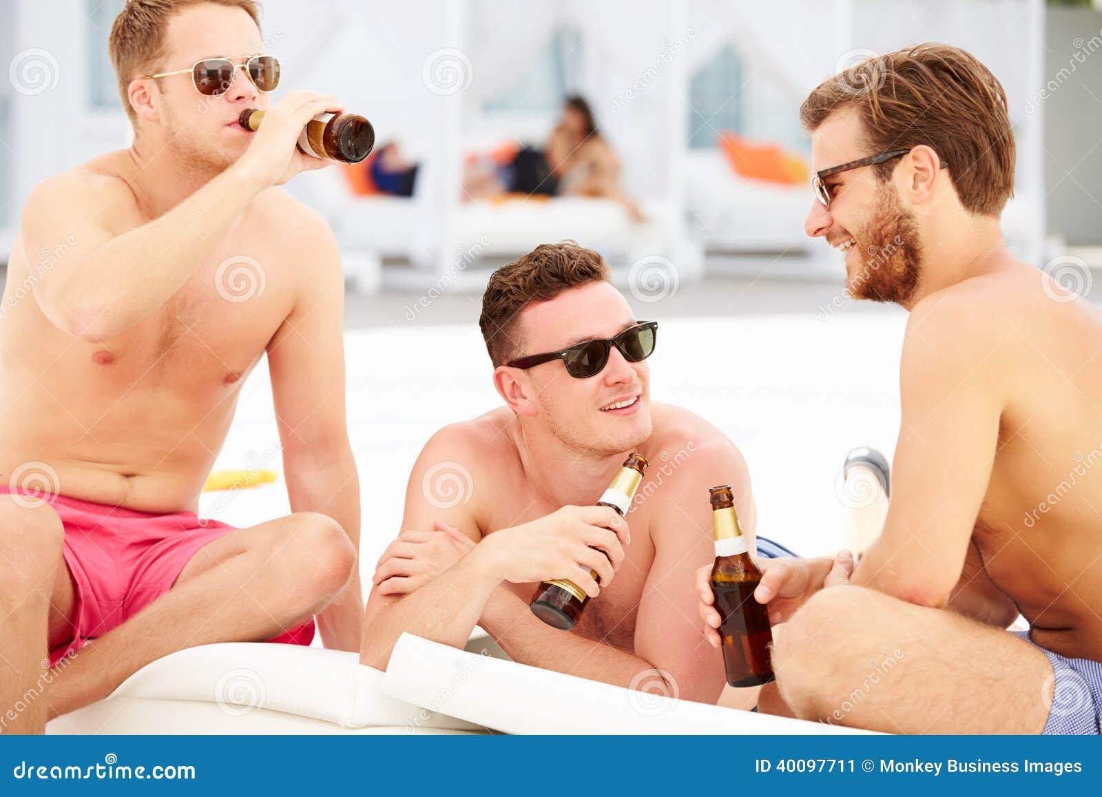 Tres amigos masculinos jovenes el día de fiesta por la piscina junto