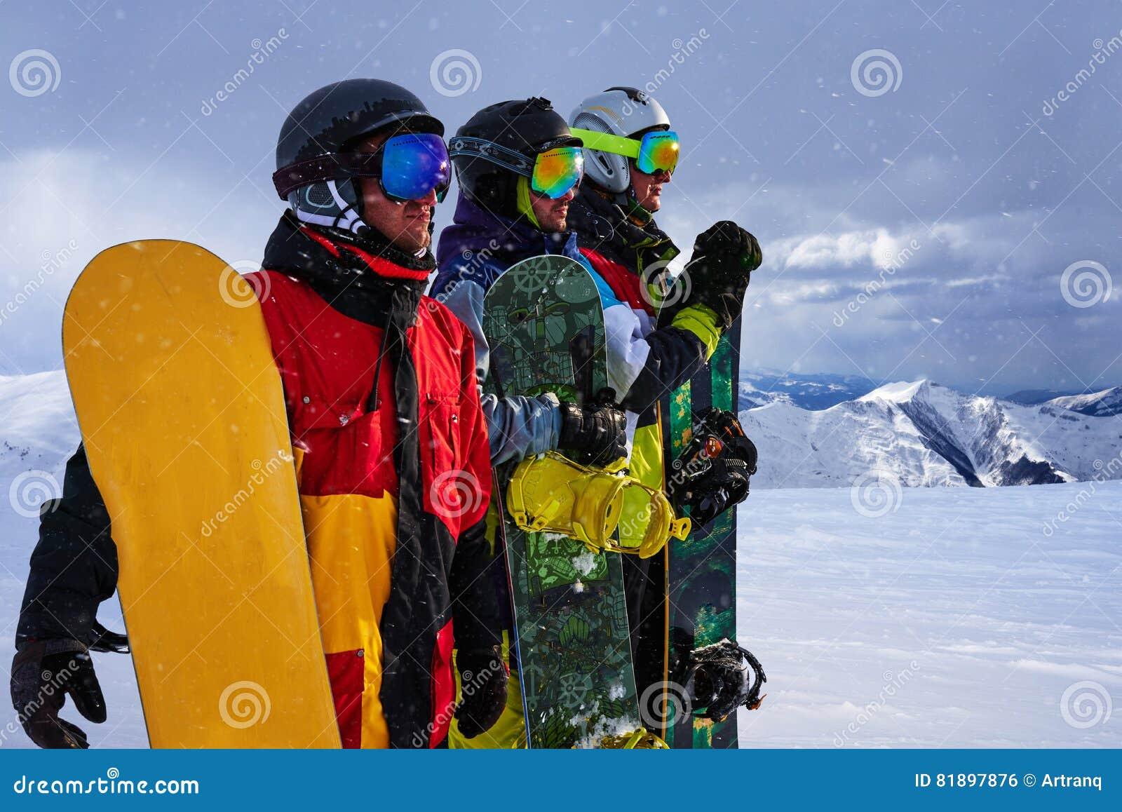 Tres amigos miran a snowboarders delanteros valeroso