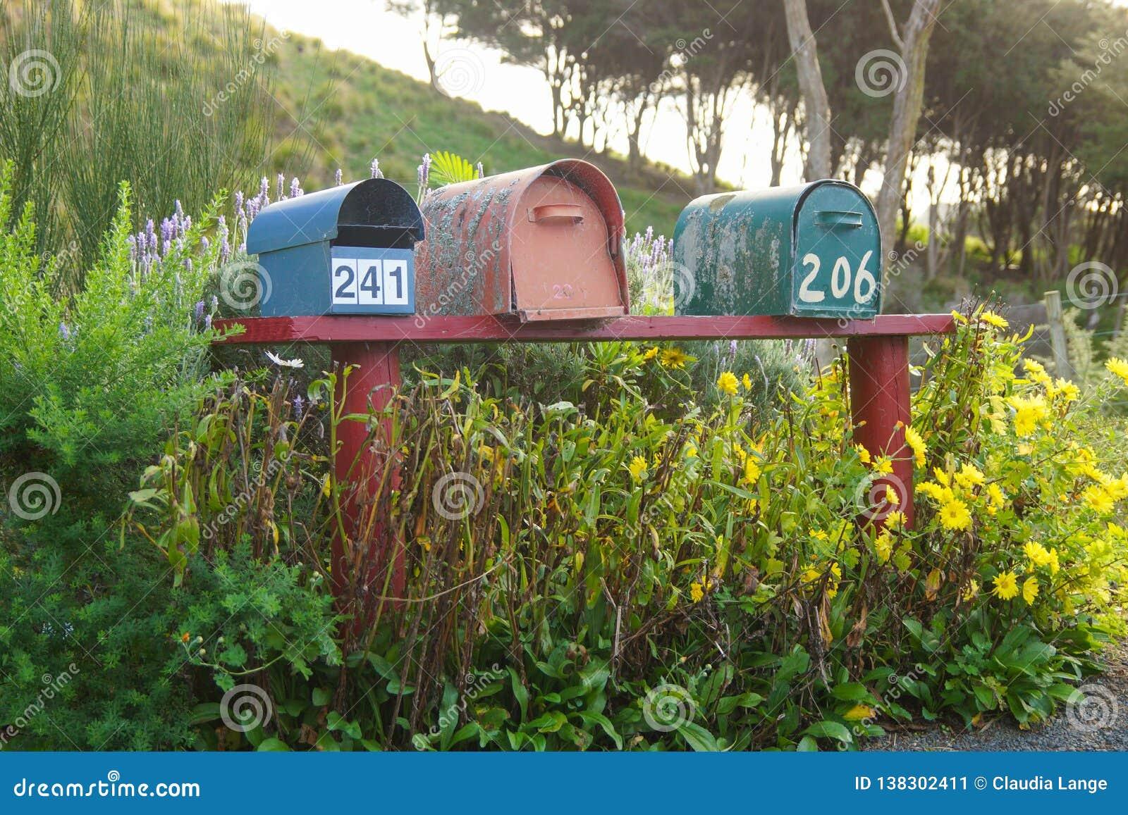 Tres buzones de correos en un banco rojo de forma de Nueva Zelanda