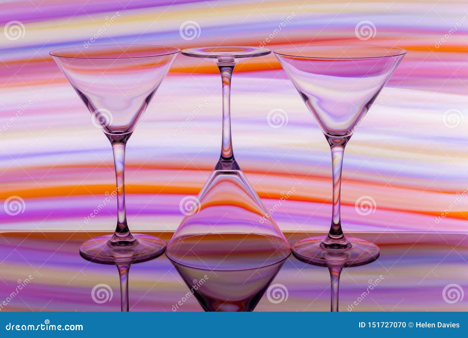 Tres cócteles/vidrios de martini en fila con un arco iris del color detrás de ellos