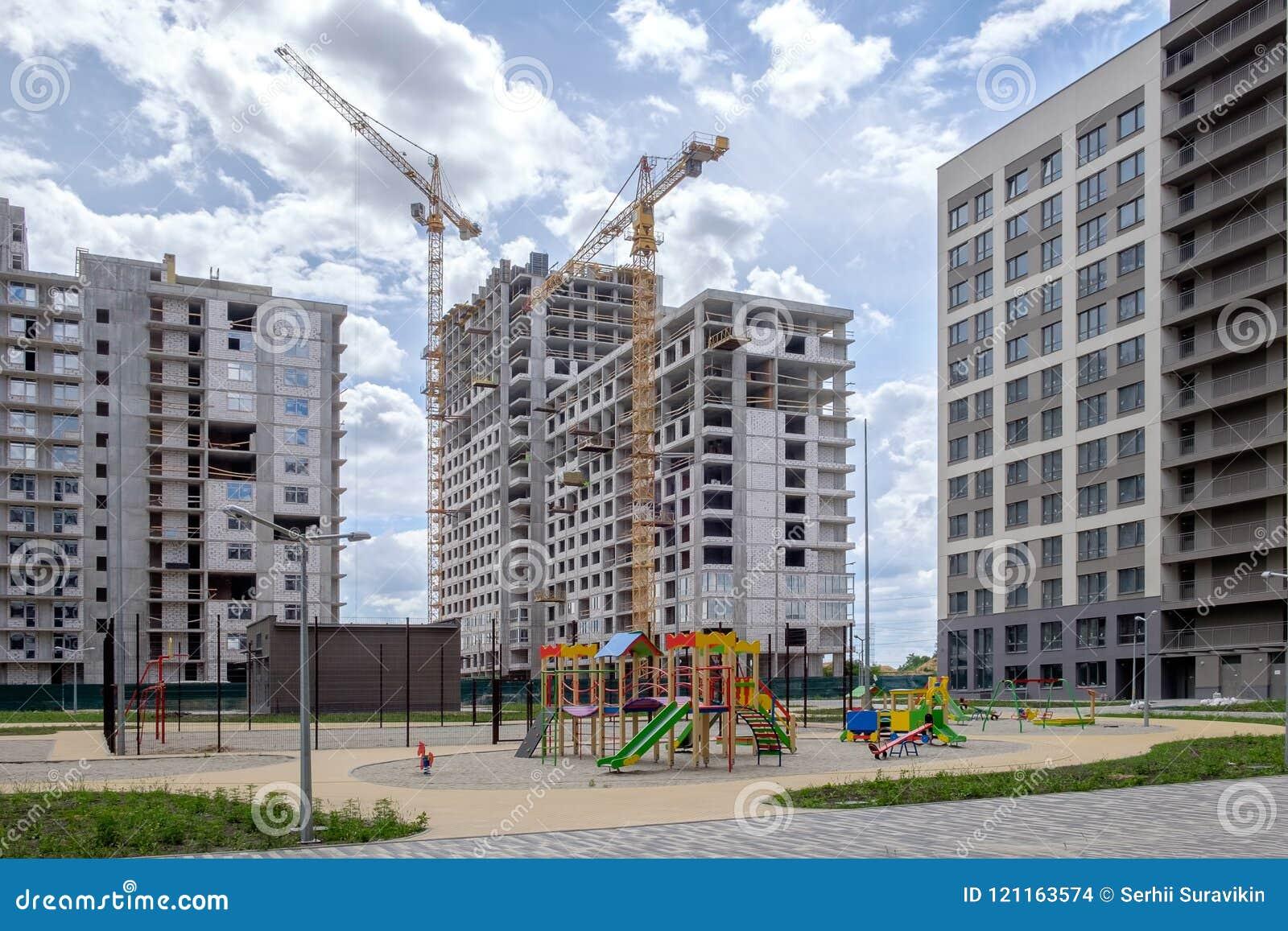 Tres casas, grúas de construcción, deportes y patios de varios pisos del ` s de los niños en el área nuevamente construida de Eur