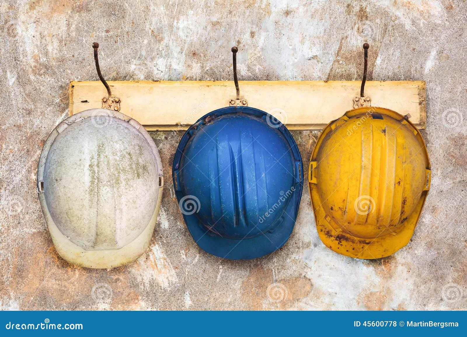 Tres cascos de la construcci n que cuelgan en un perchero for Que es un perchero