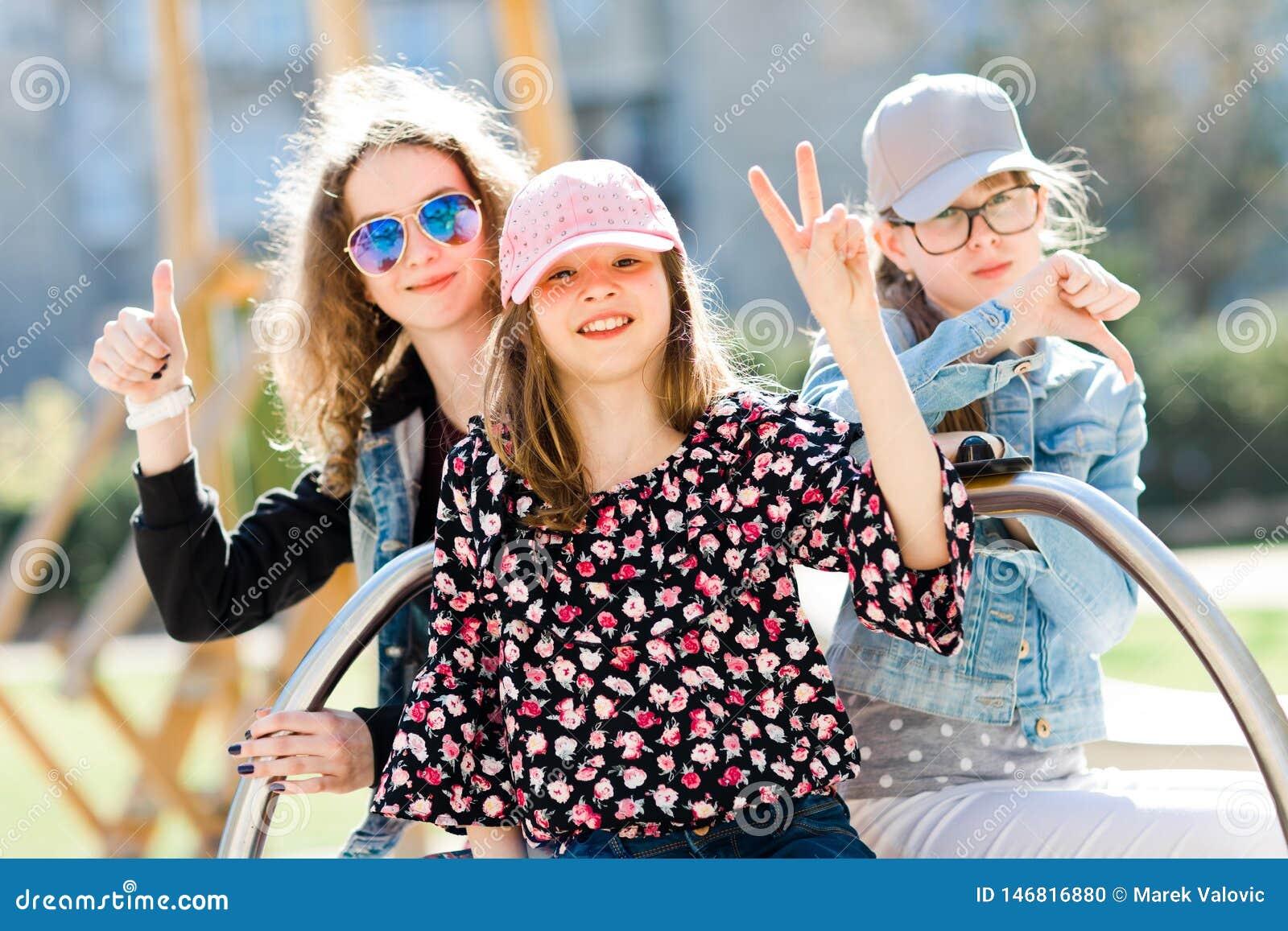 Tres chicas jóvenes en el patio que se sienta en el pequeño carrusel - la victoria, golpea pesadamente para arriba y golpear pesa