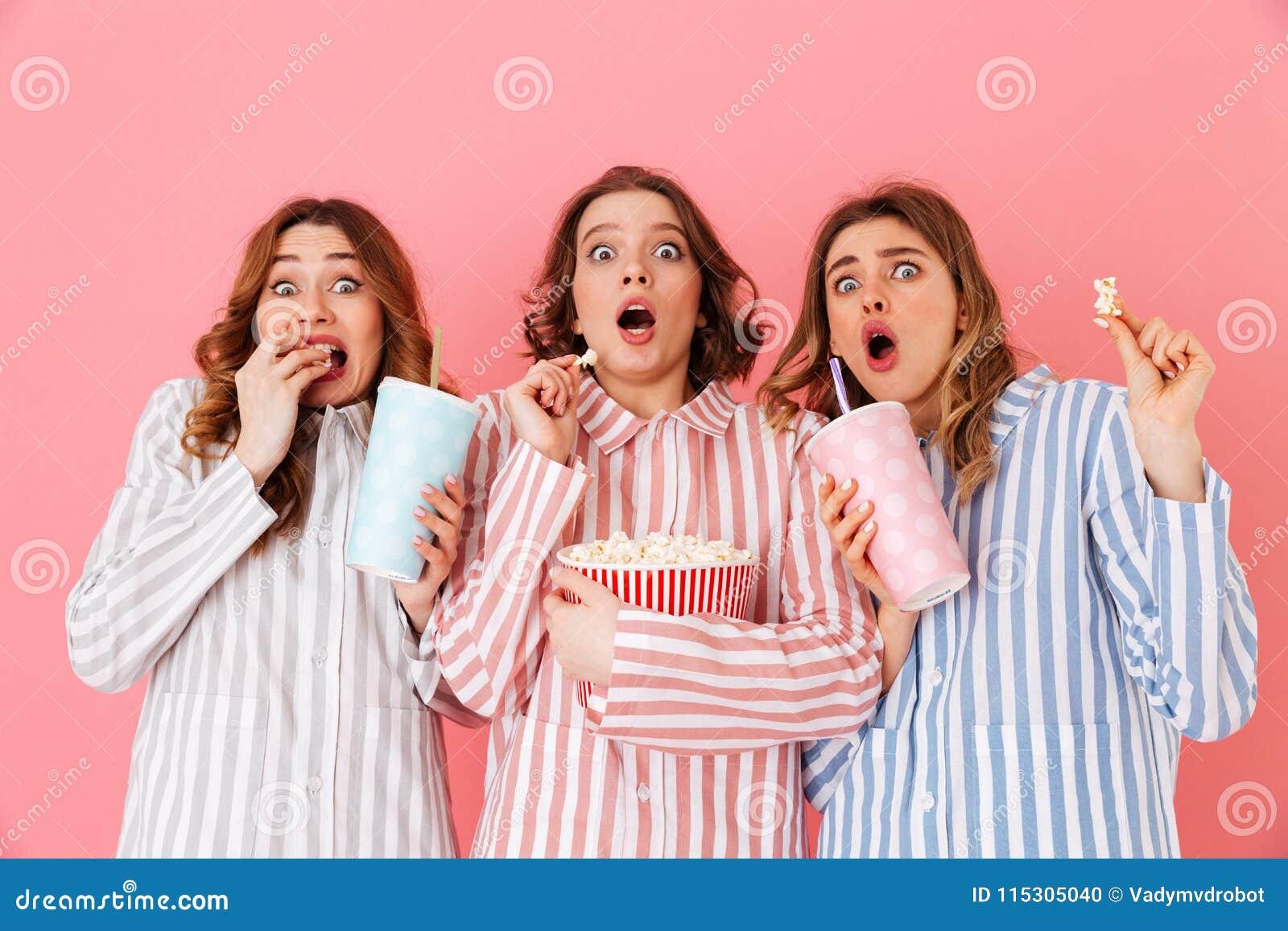 Tres chicas jóvenes 20s que llevan expressin rayado colorido de los pijamas