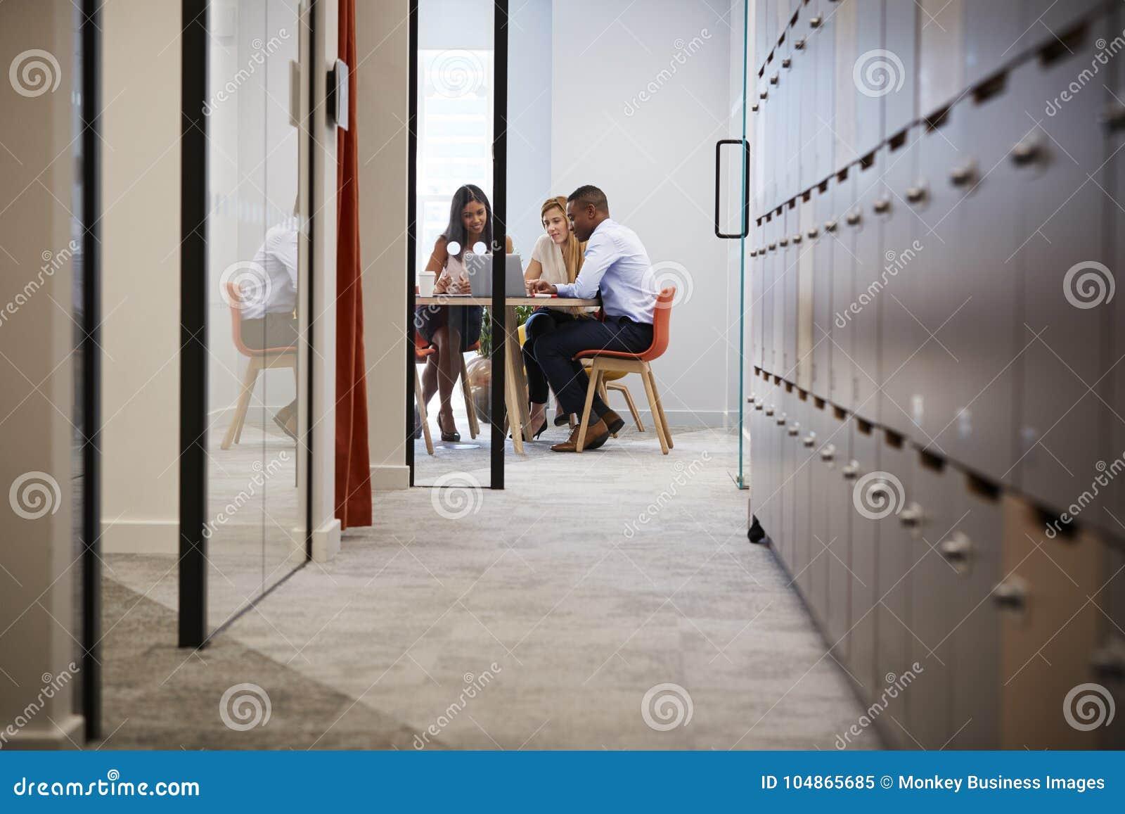 Tres colegas que usan el ordenador portátil en una reunión de la oficina