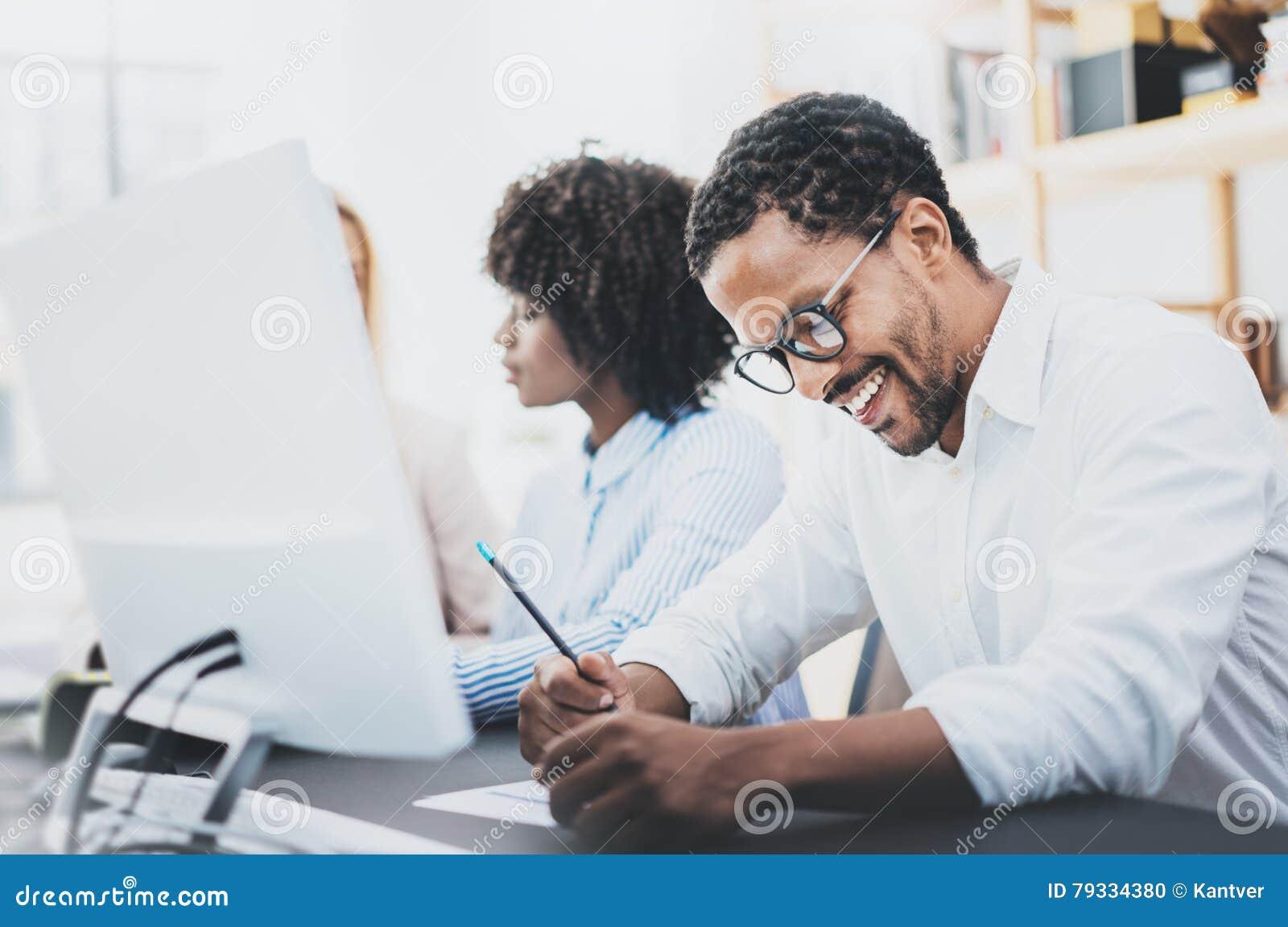 Tres compañeros de trabajo jovenes que trabajan junto en una oficina moderna Hombre afroamericano en la camisa blanca que sonríe