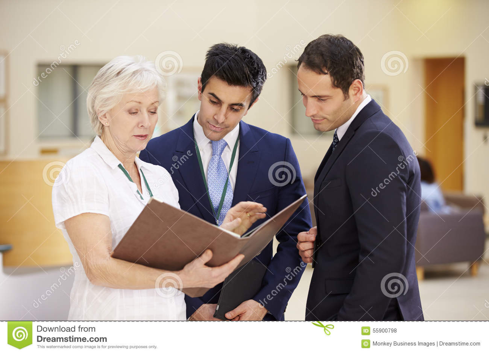 Tres consultores que discuten notas pacientes en hospital