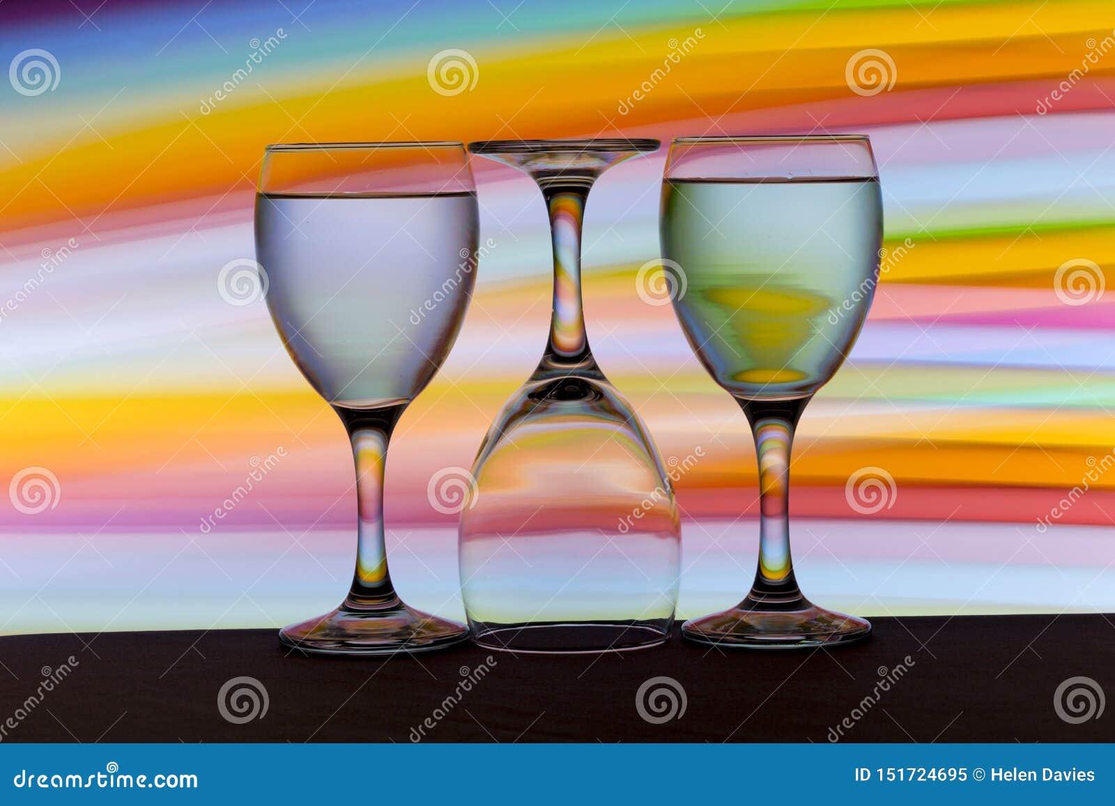 Tres copas de vino en fila con un arco iris del color detrás de ellos