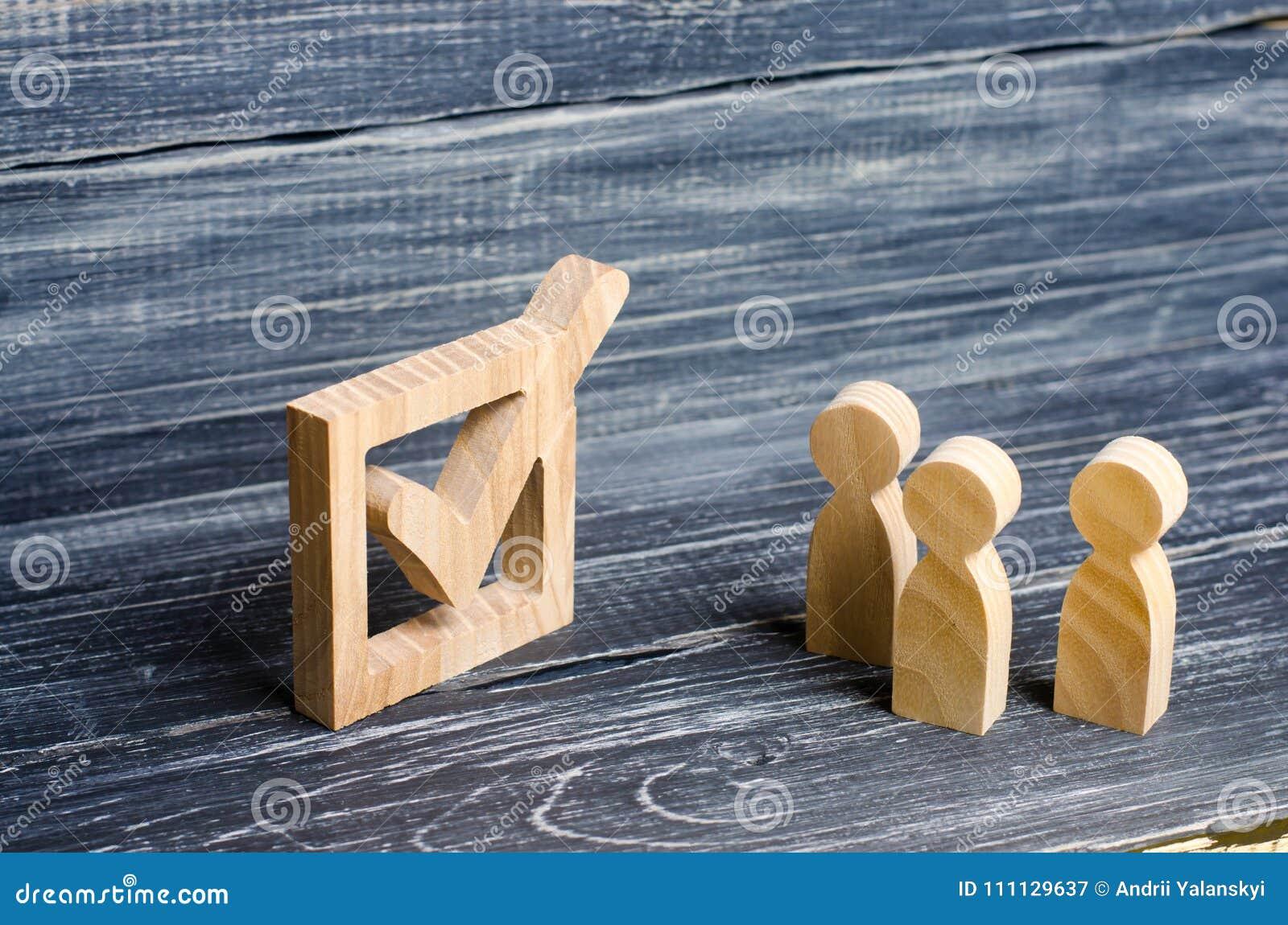 Tres figuras humanas de madera se unen al lado de una señal en