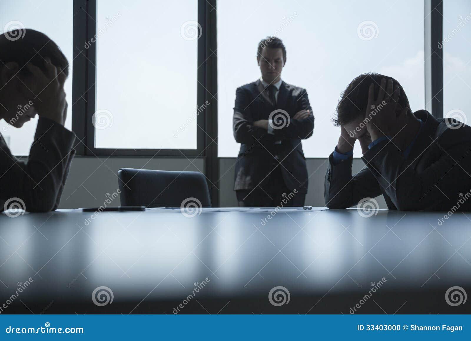 Tres frustrados y hombres de negocios trabajados demasiado en la sala de juntas con los brazos cruzados y principales en manos.