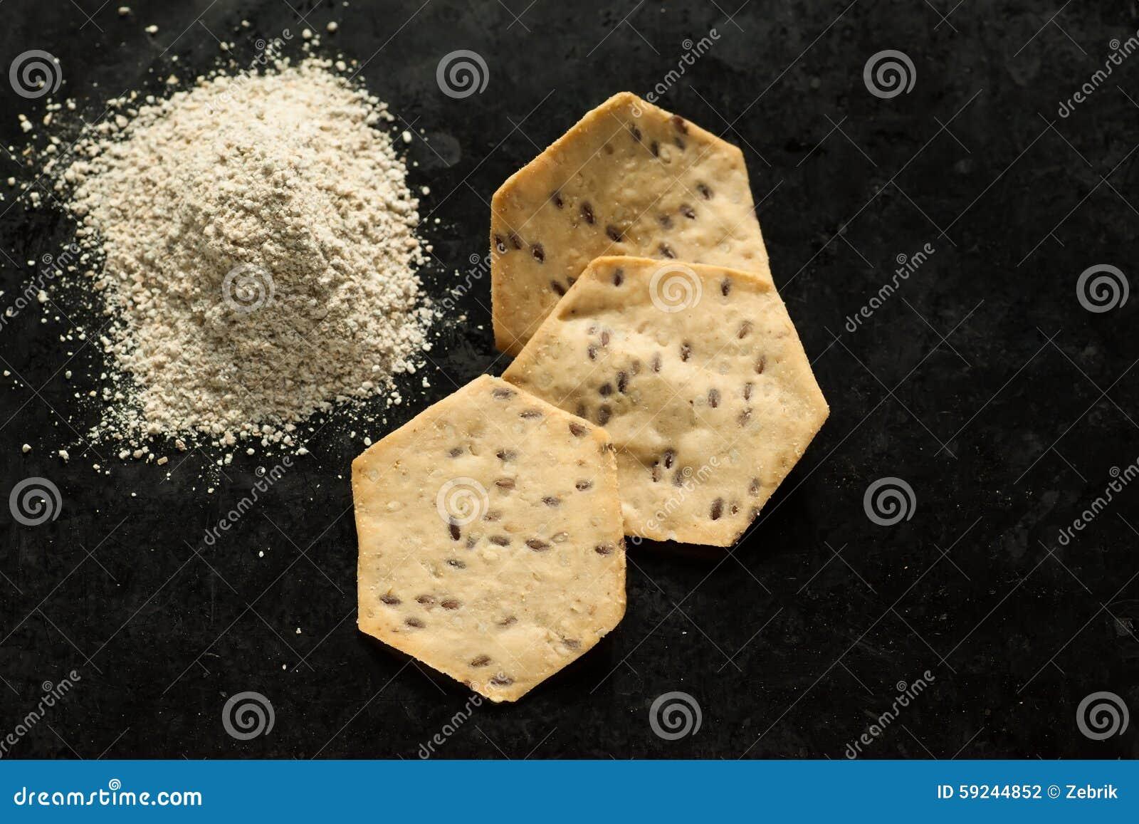 Tres galletas orgánicas y harina del grano entero en el horno-p negro