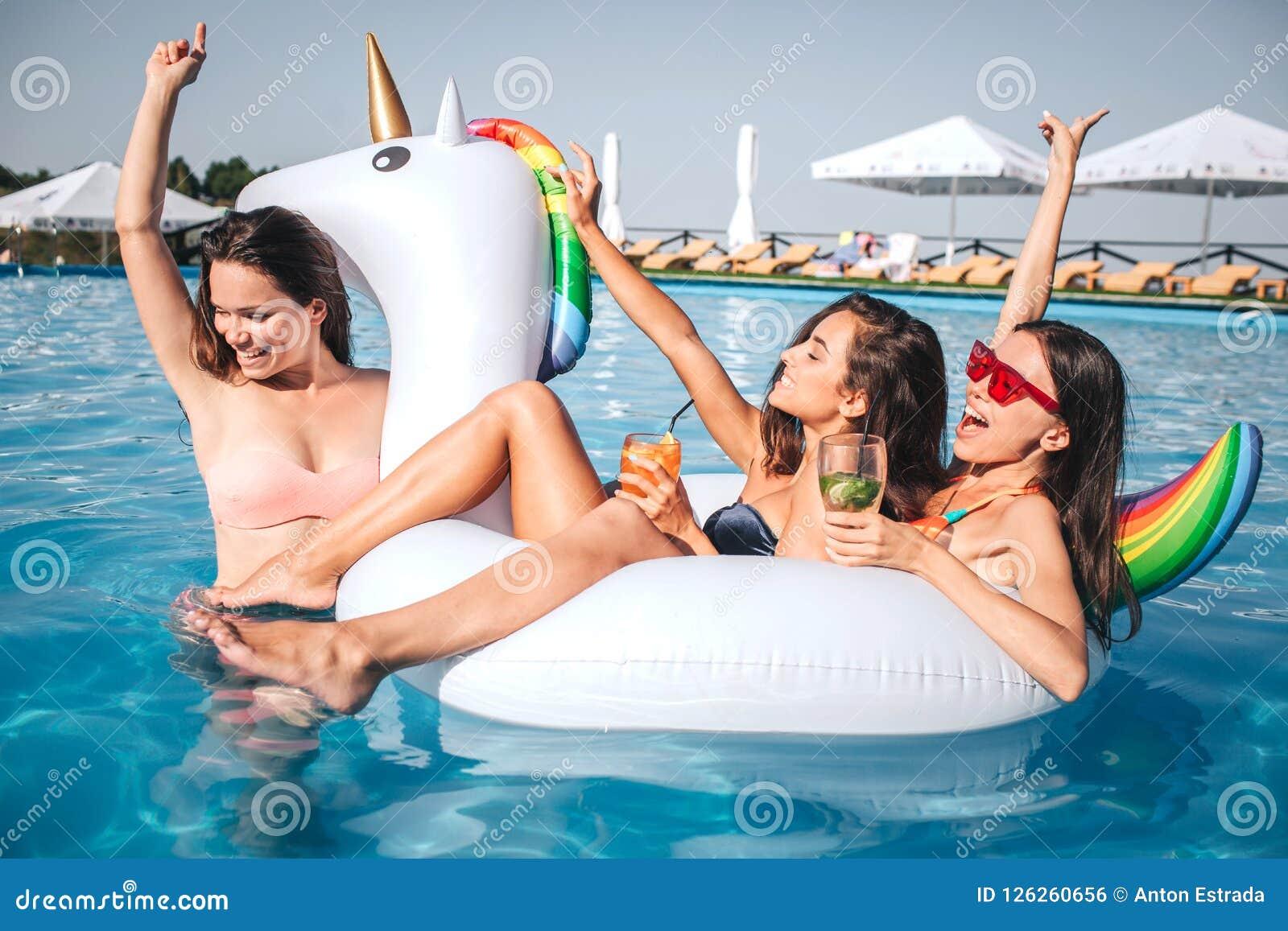 Tres modelos magníficos están en piscina Dos de ellos se sientan en el flotador formado unicornio Thirl uno lo sostiene en su cue