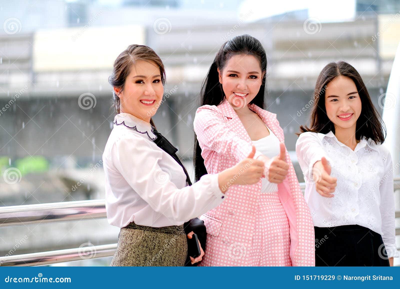 Tres muchachas asiáticas del negocio están actuando con los pulgares para arriba para su trabajo y están sonriendo para expresar