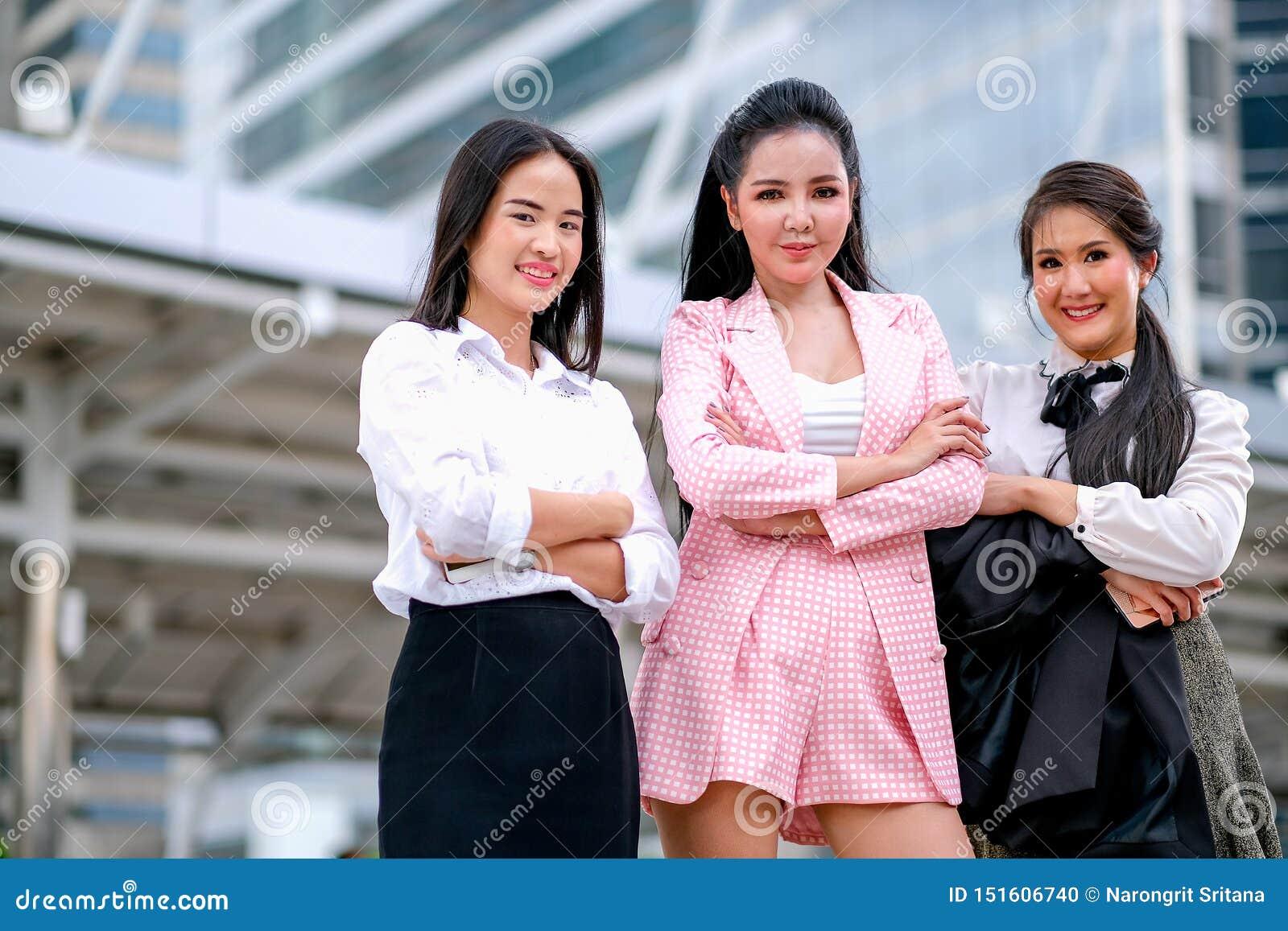 Tres muchachas asiáticas del negocio están actuando tan confiadas con su trabajo y están sonriendo para expresar de feliz durante