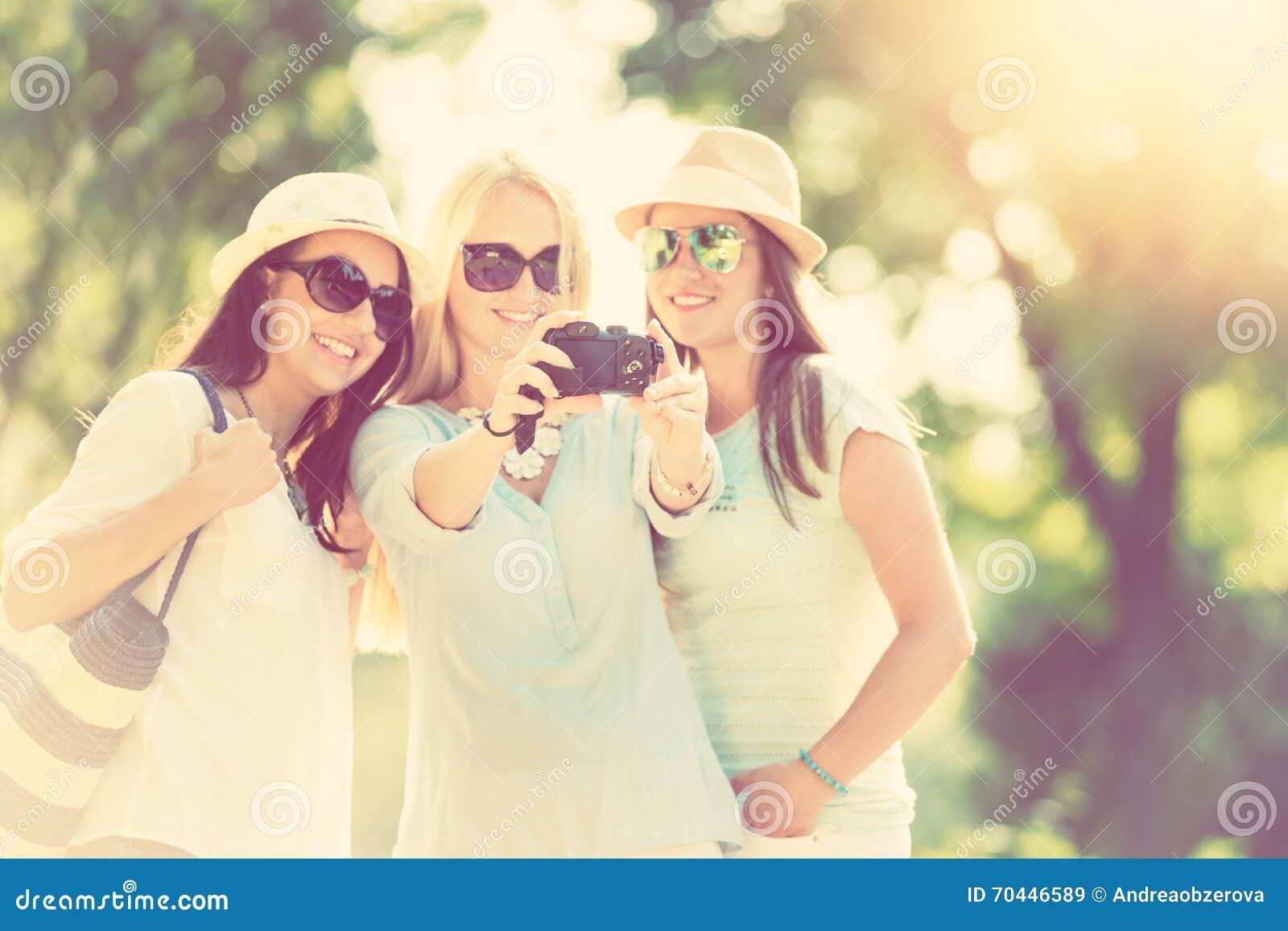 Tres muchachas atractivas que toman la imagen en las vacaciones de verano