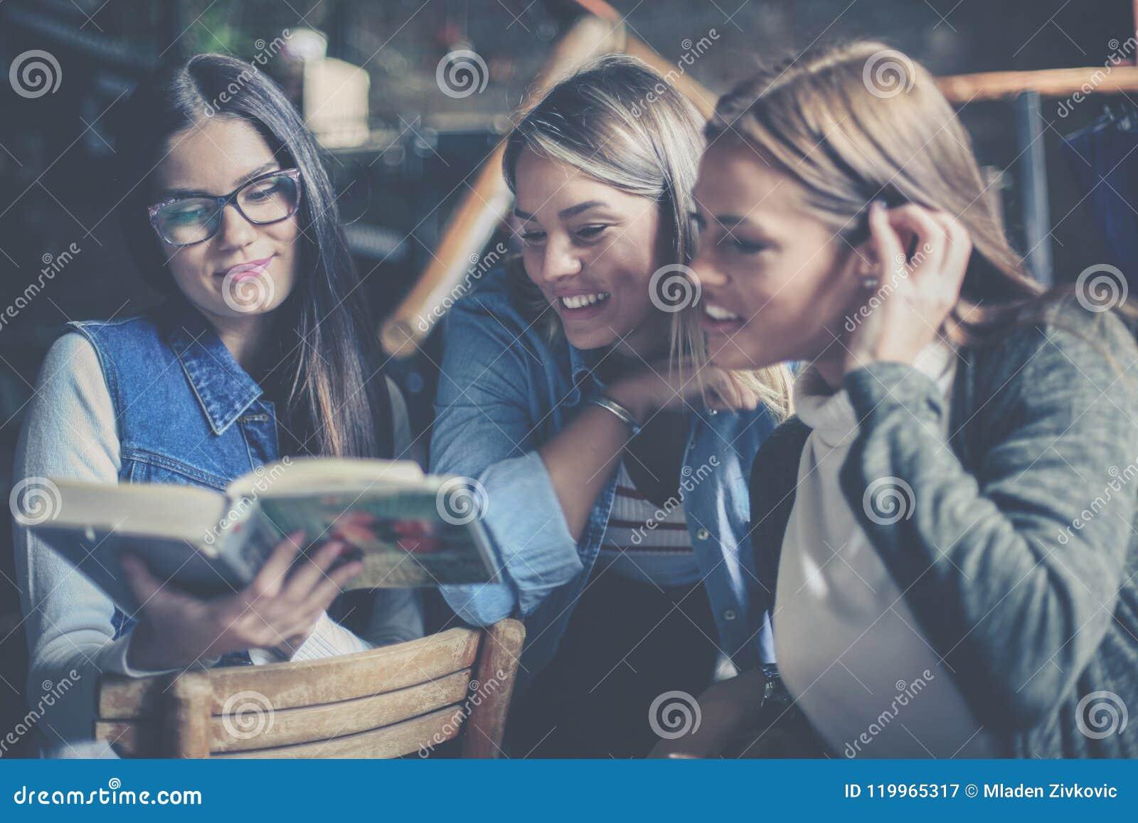 Tres muchachas de los estudiantes que estudian junto en biblioteca