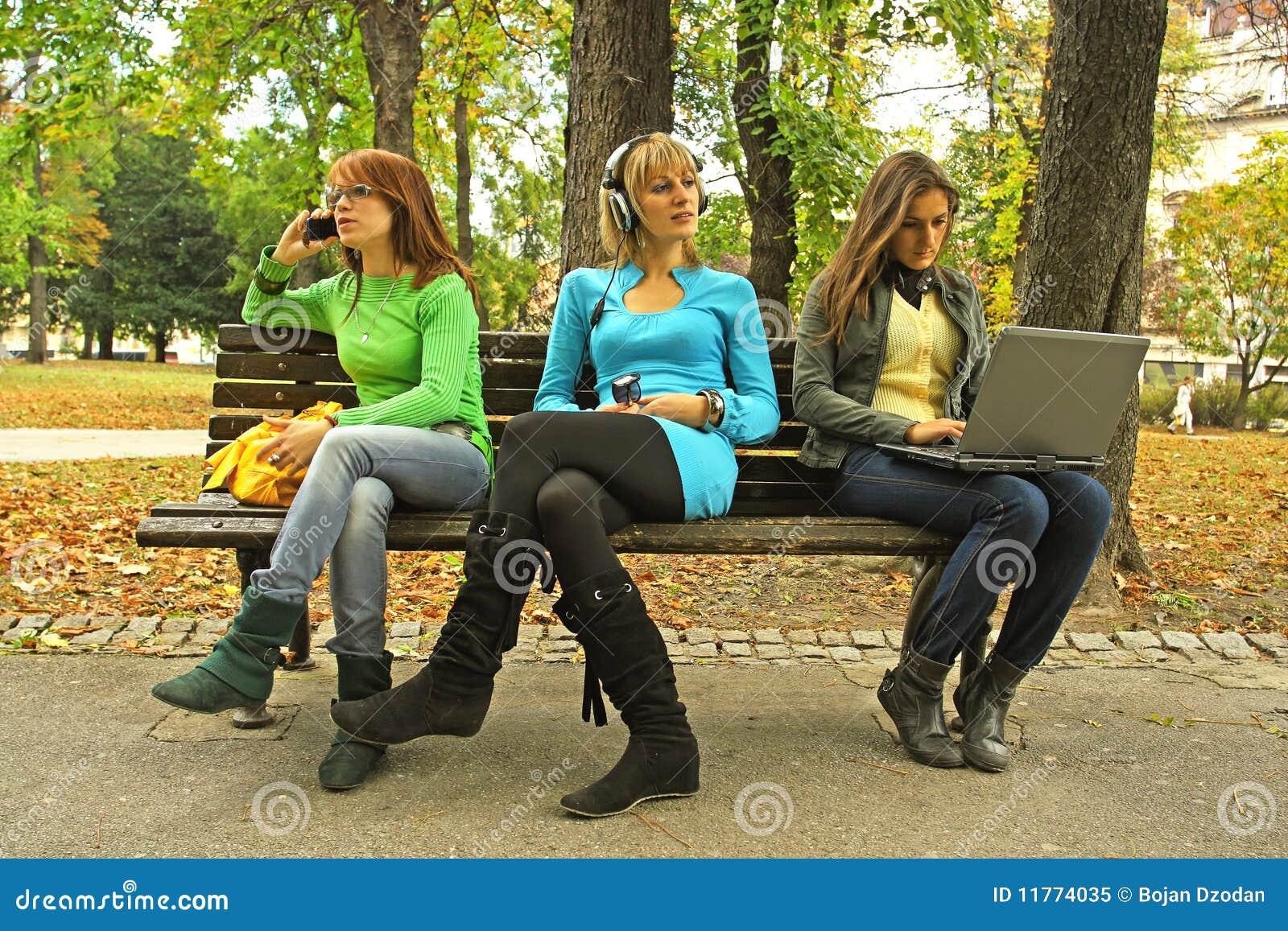 Tres muchachas en un banco