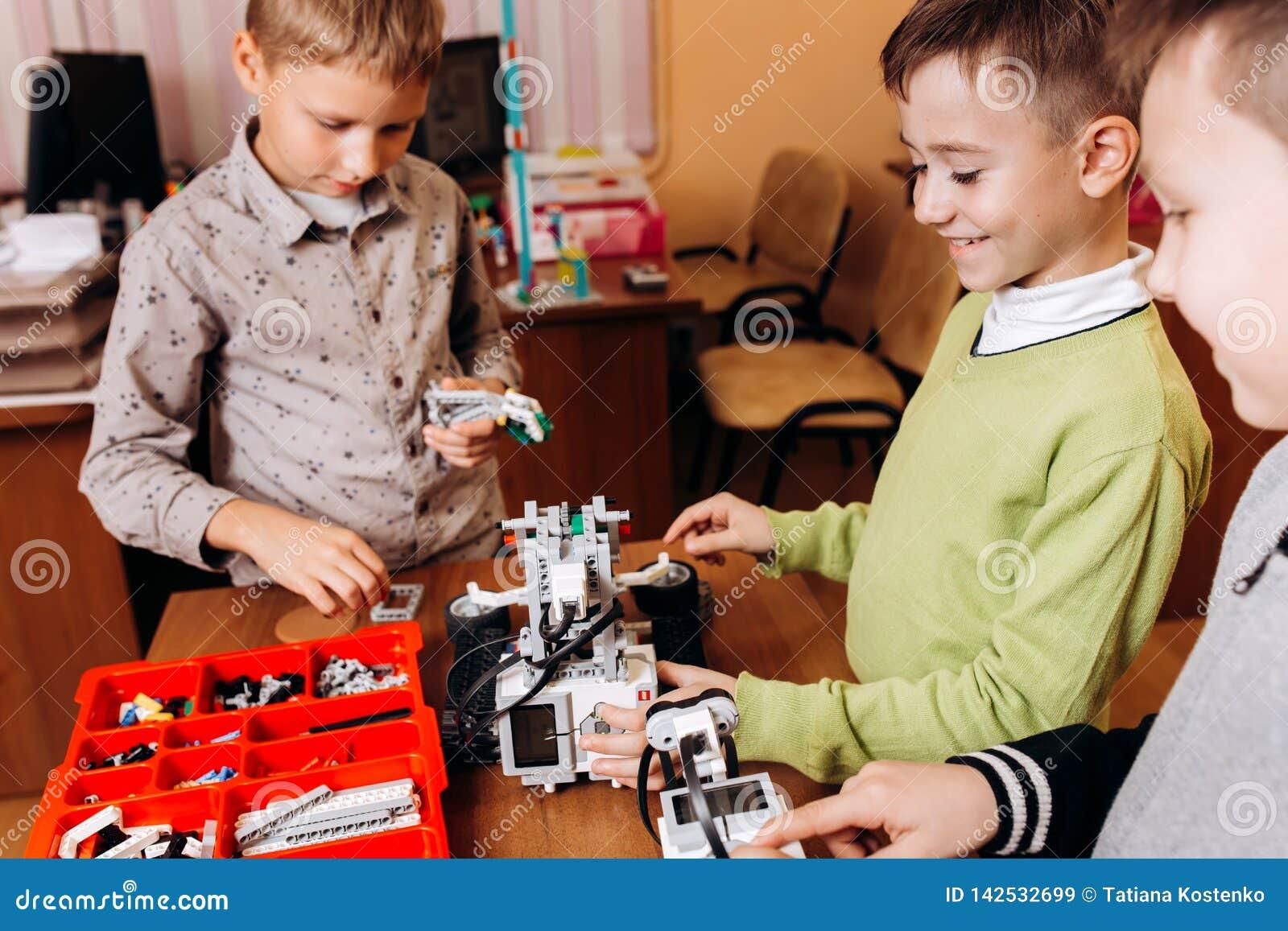 Tres muchachos felices están haciendo los robots en la escuela de la robótica