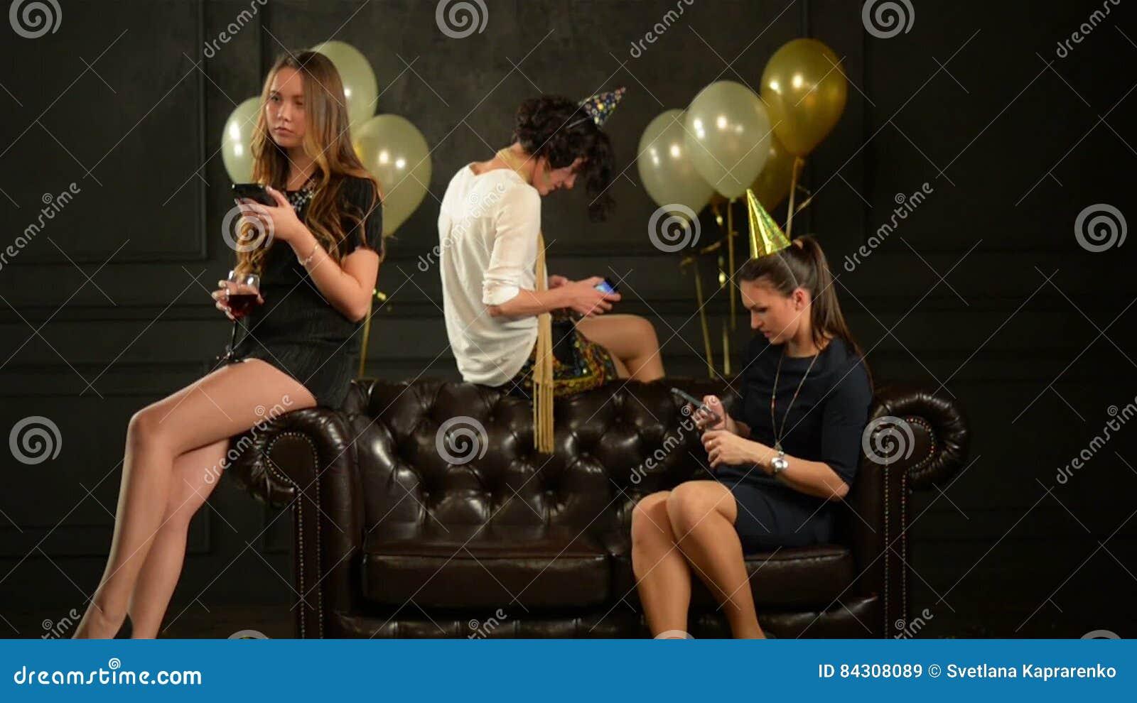 ac833d0f1 Tres Mujeres En Vestidos Cortos Usando Sus Smartphones Durante Una Celebración  Al Lado Del Sofá De Brown Oscuro Las Chicas Marcho Almacen De Video - Vídeo  ...