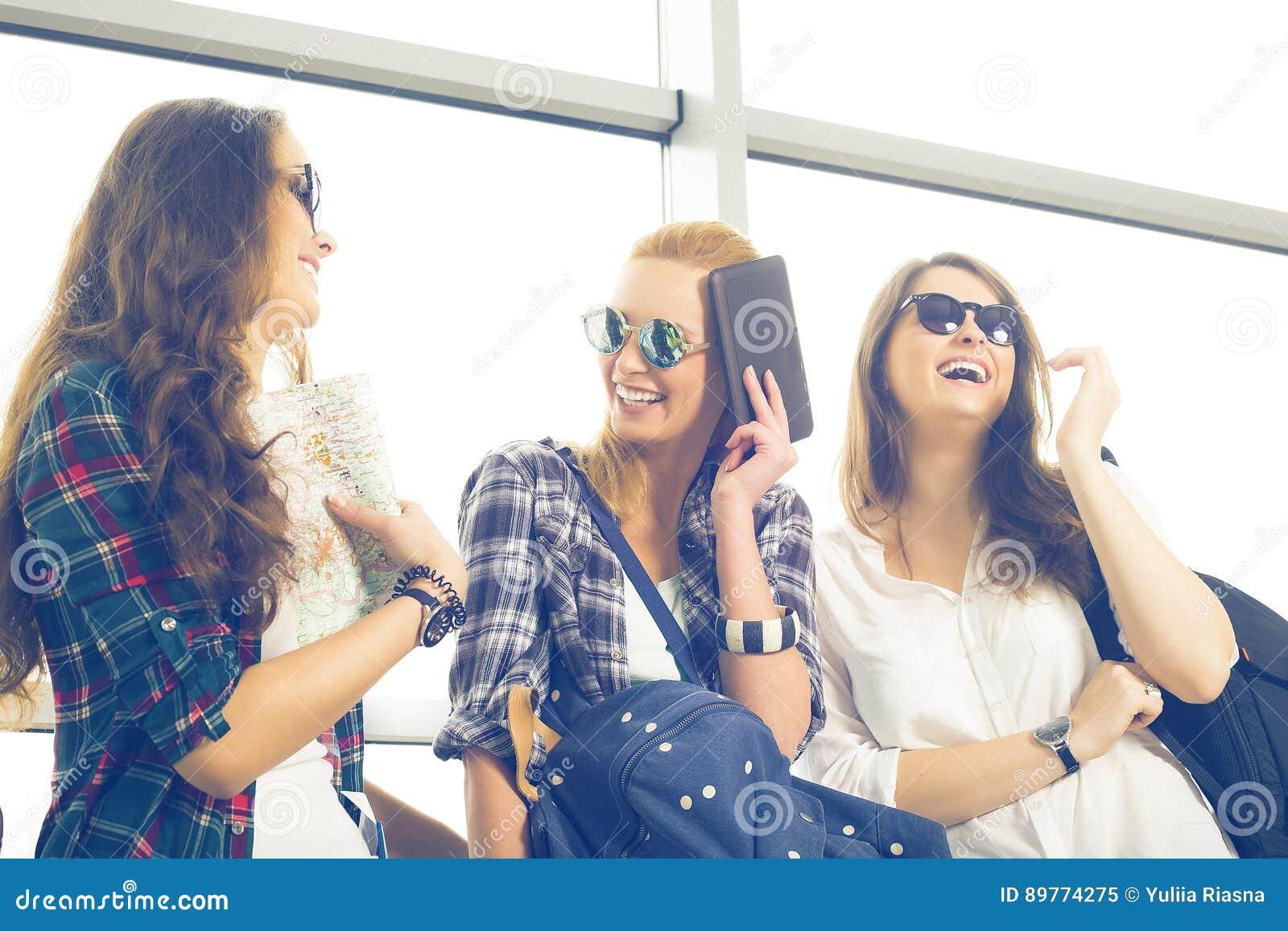 Tres mujeres jovenes en las gafas de sol que se colocan en el aeropuerto y la risa Un viaje con los amigos