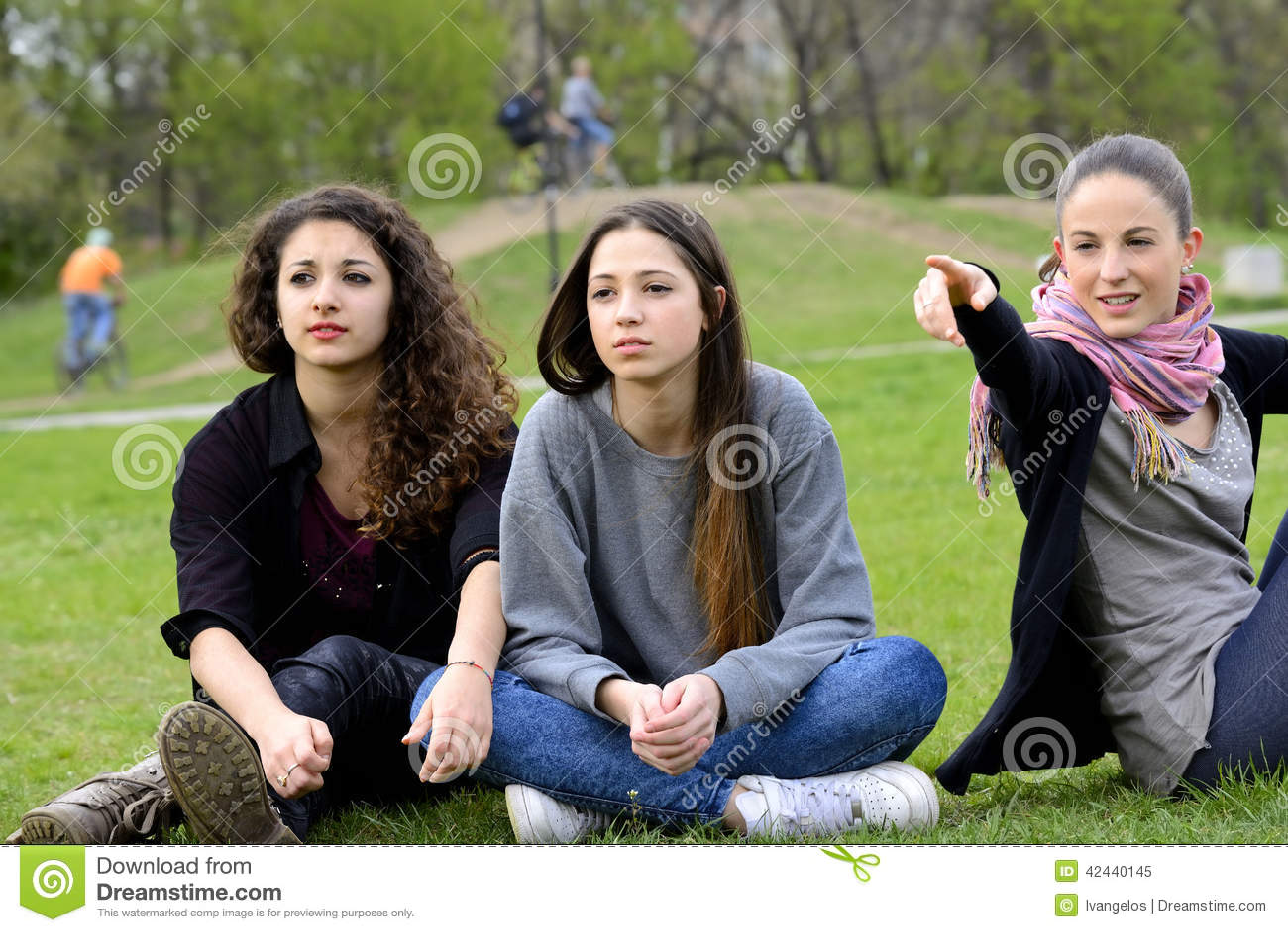 Tres mujeres jovenes que miran y que señalan
