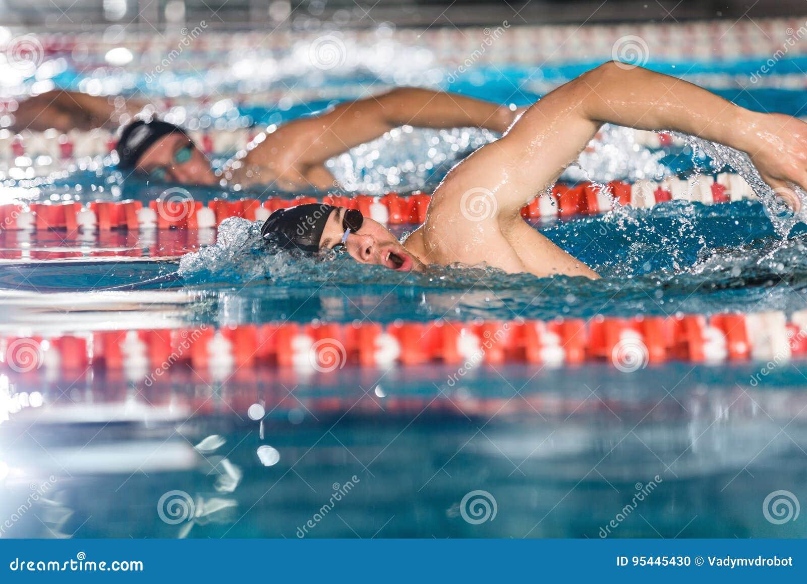 Tres nadadores de sexo masculino que hacen estilo libre en diversos carriles de natación