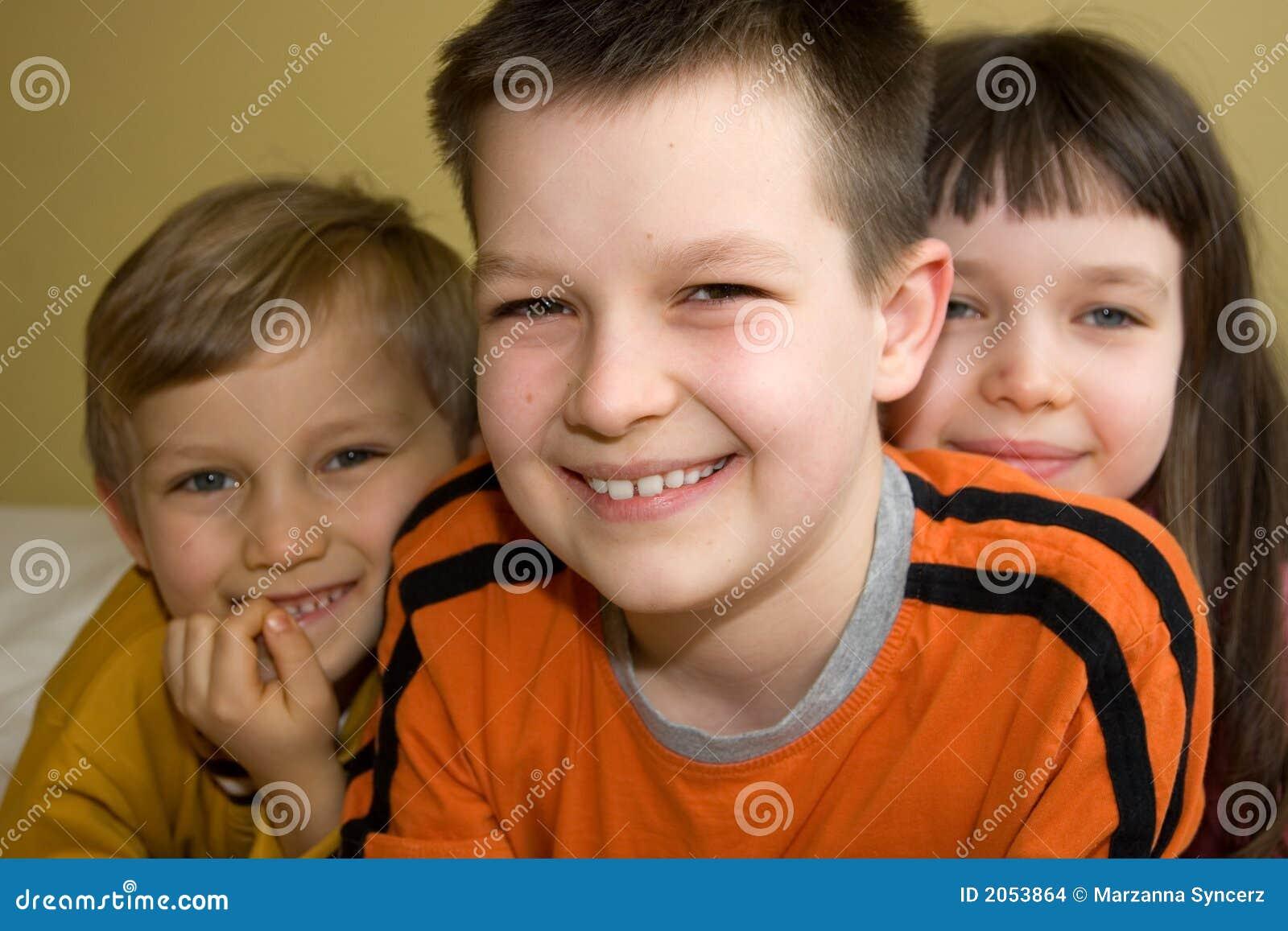 Tres niños con sonrisas de emisión