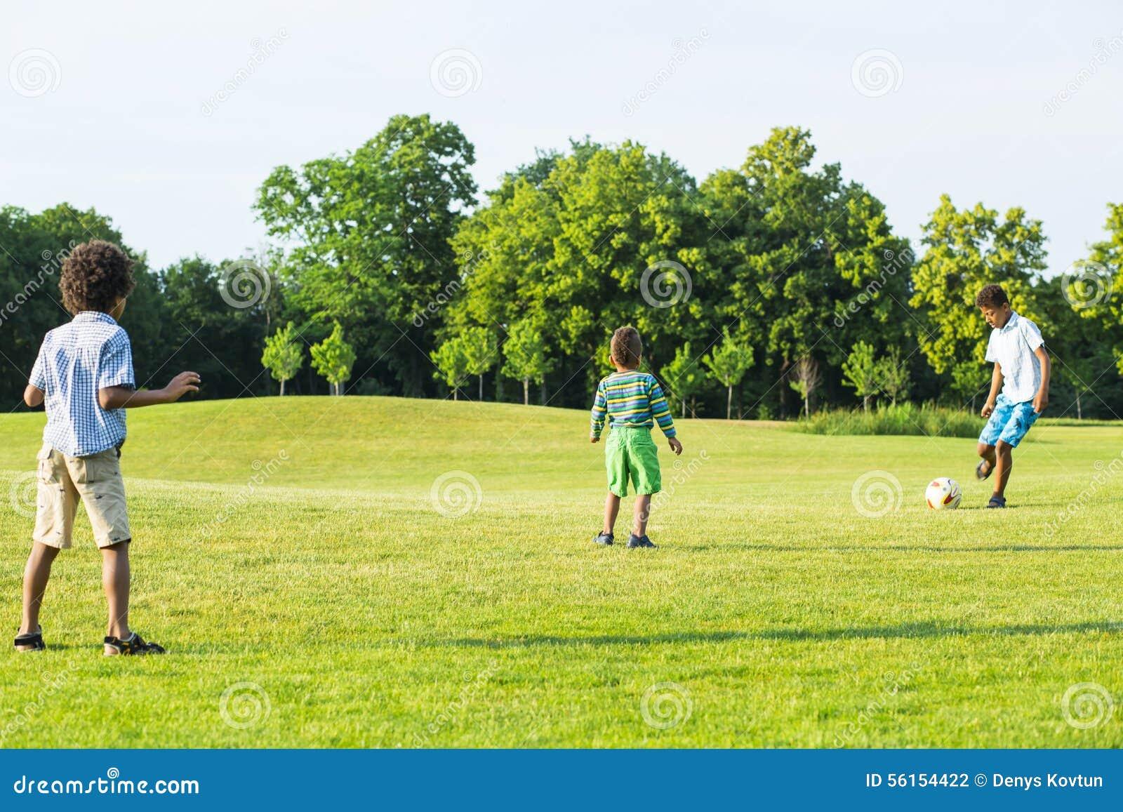 Tres Ninos Estan Jugando A Futbol Foto De Archivo Imagen De Lindo