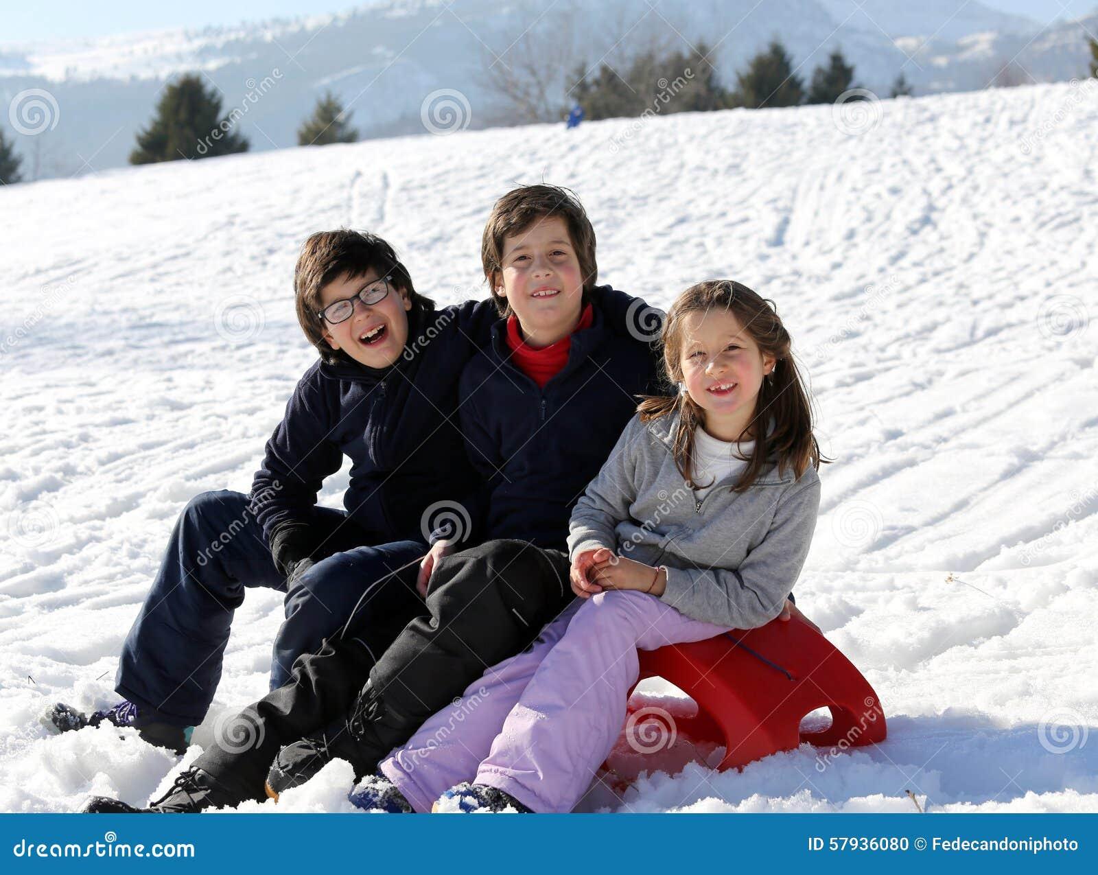 Tres niños felices en nieve durante las vacaciones de verano