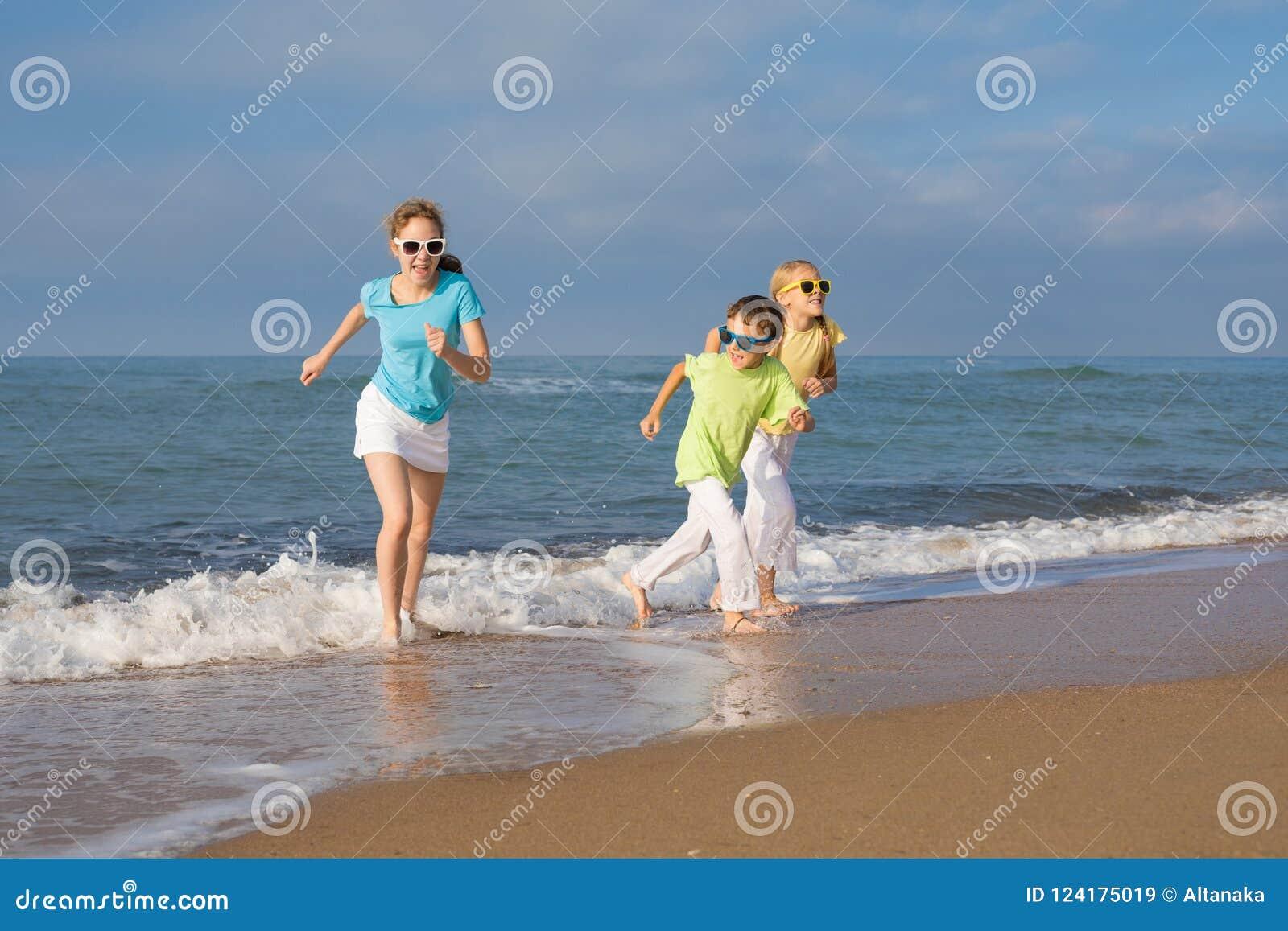 Tres niños felices que corren en la playa en el tiempo del día
