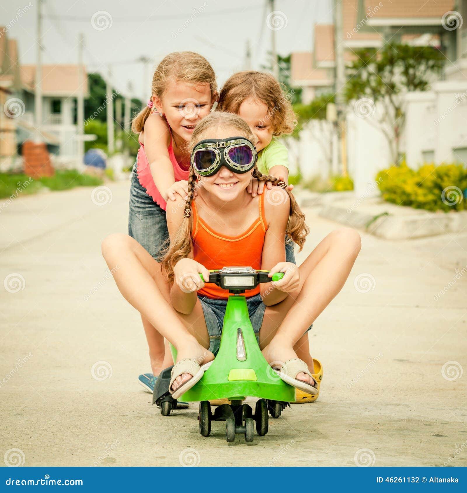 Tres niños felices que juegan en el camino