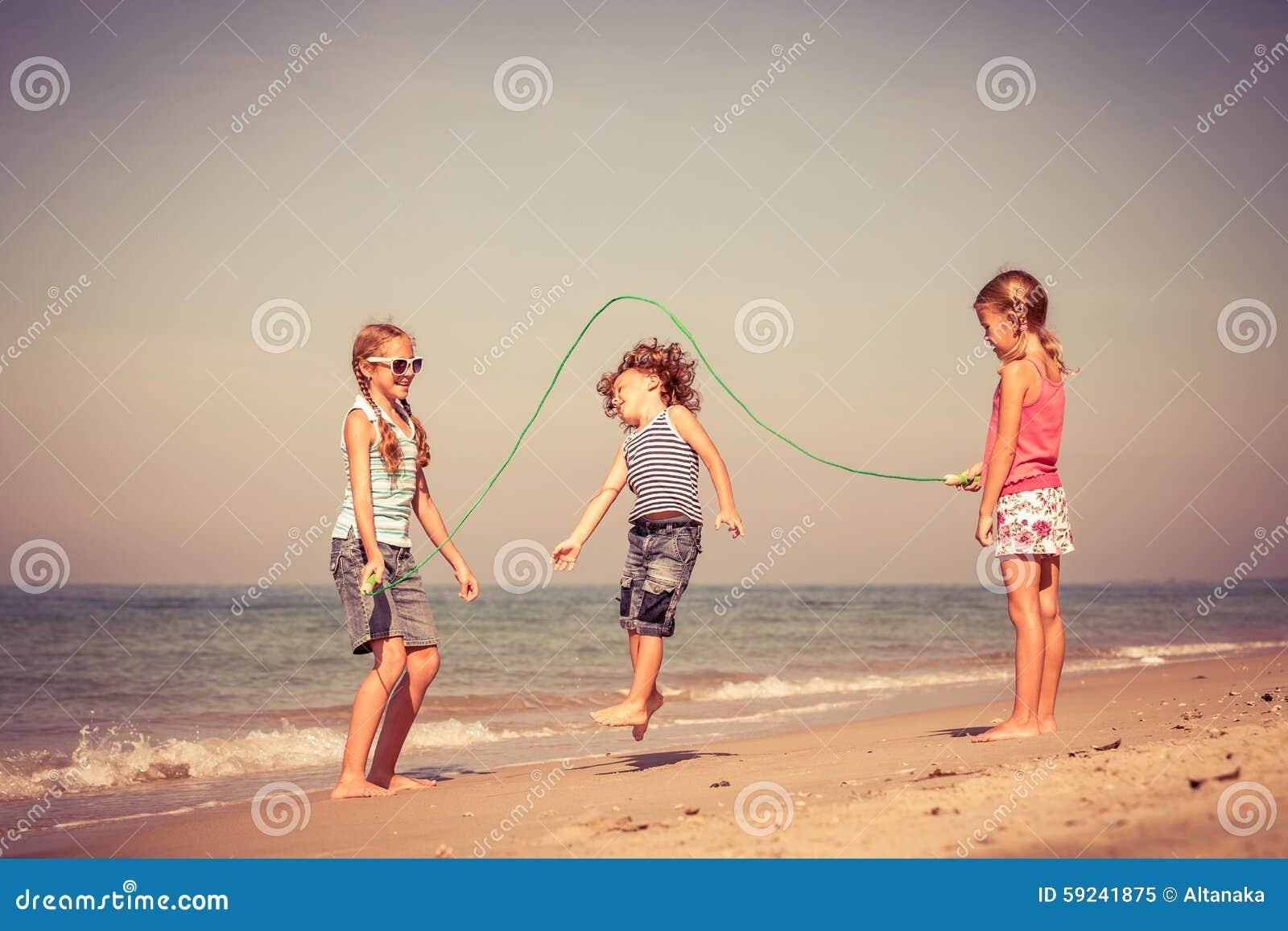 Tres niños felices que juegan en la playa