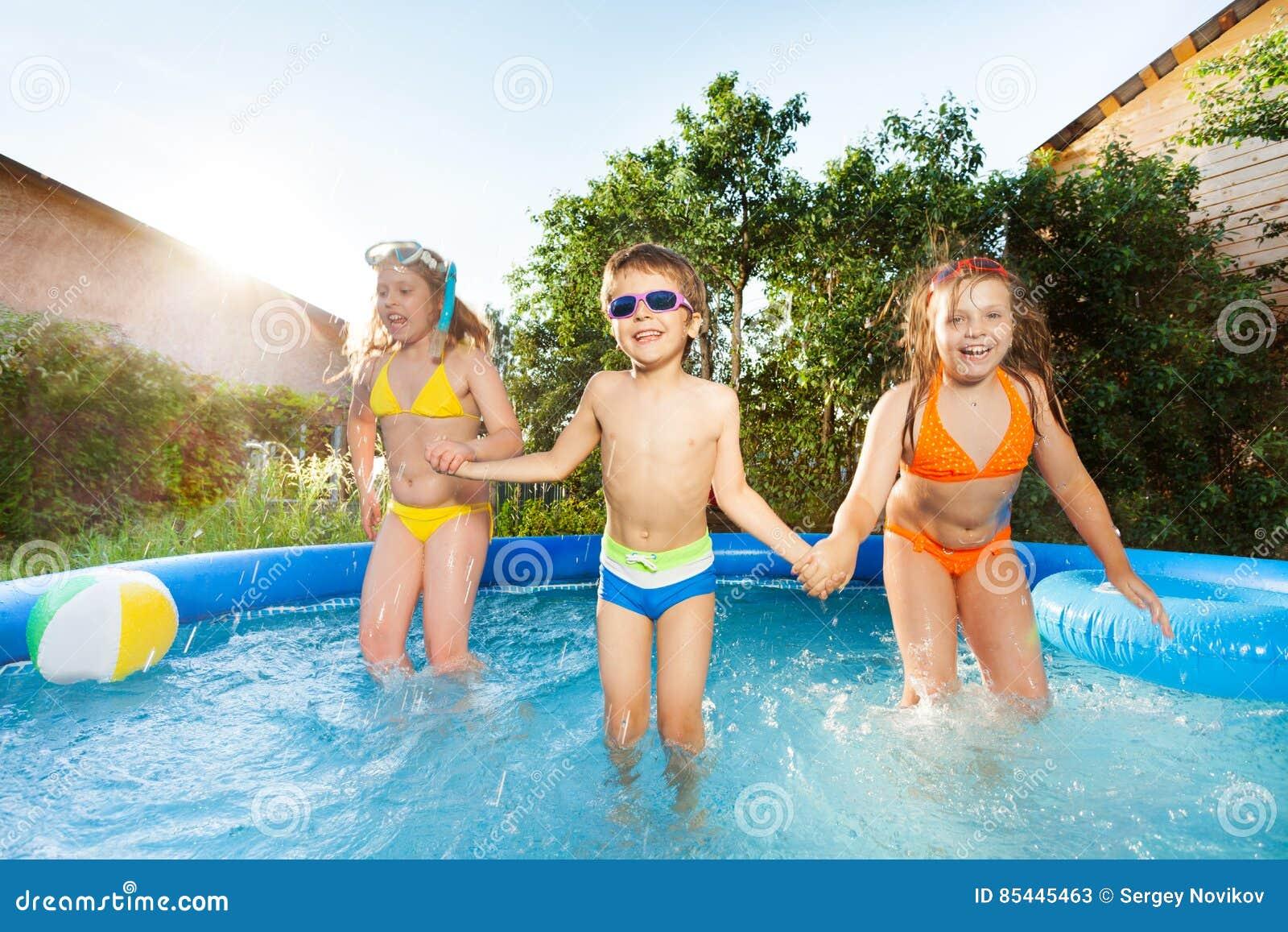 Tres niños felices que saltan en la piscina