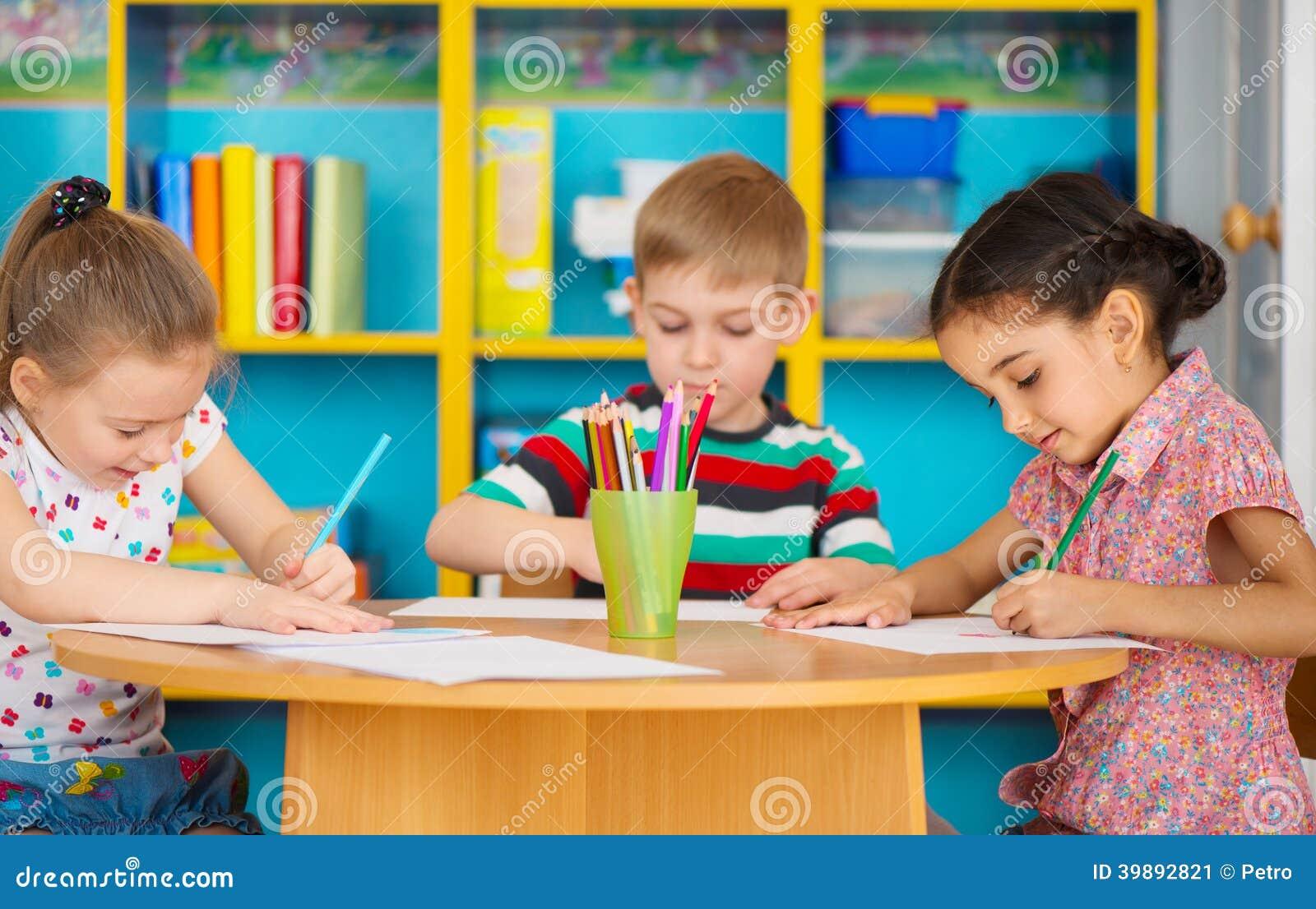 Tres niños preescolares que dibujan en la guardería
