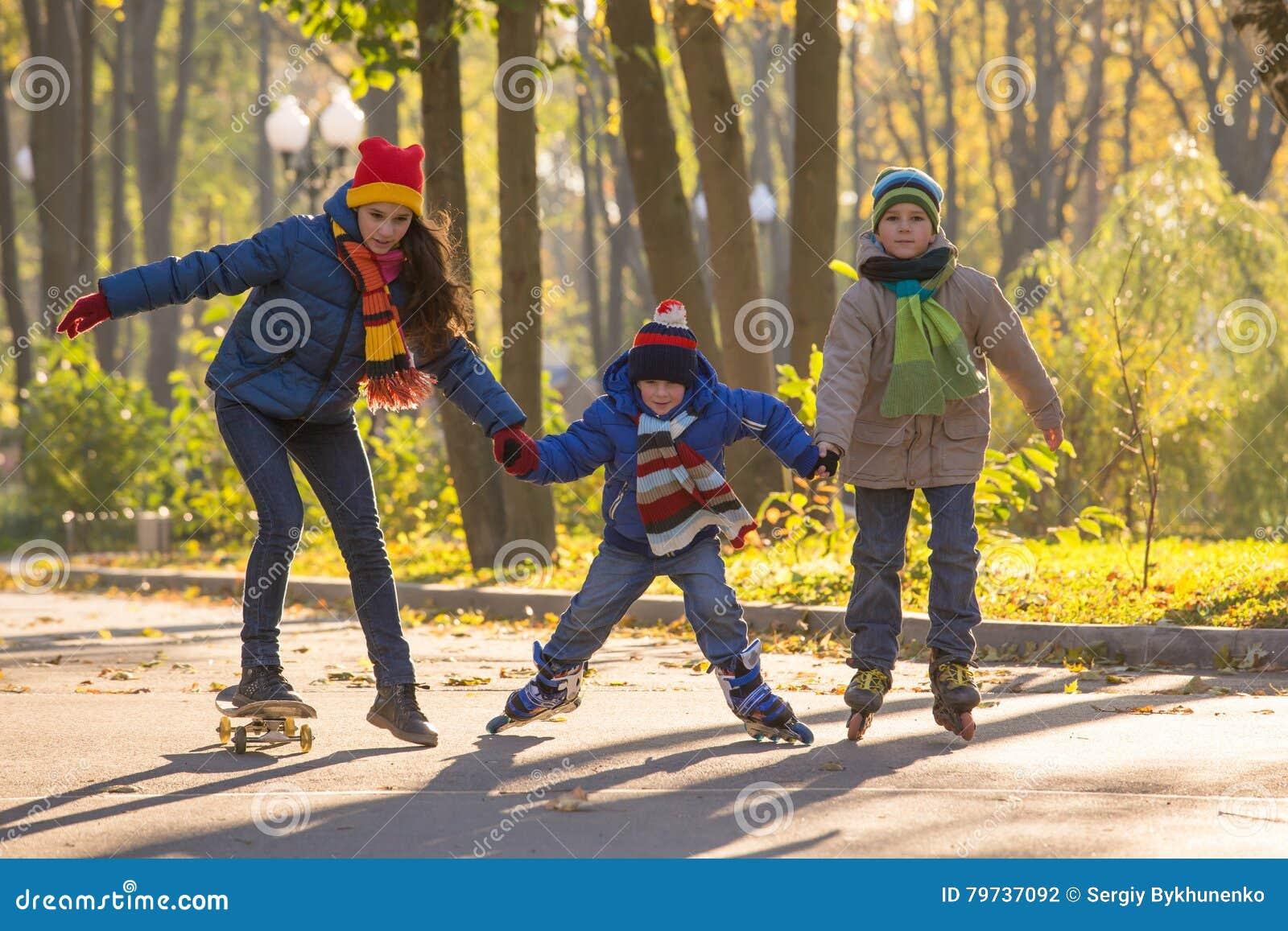 Tres niños que aprenden montar en parque del otoño en rollerblades y s