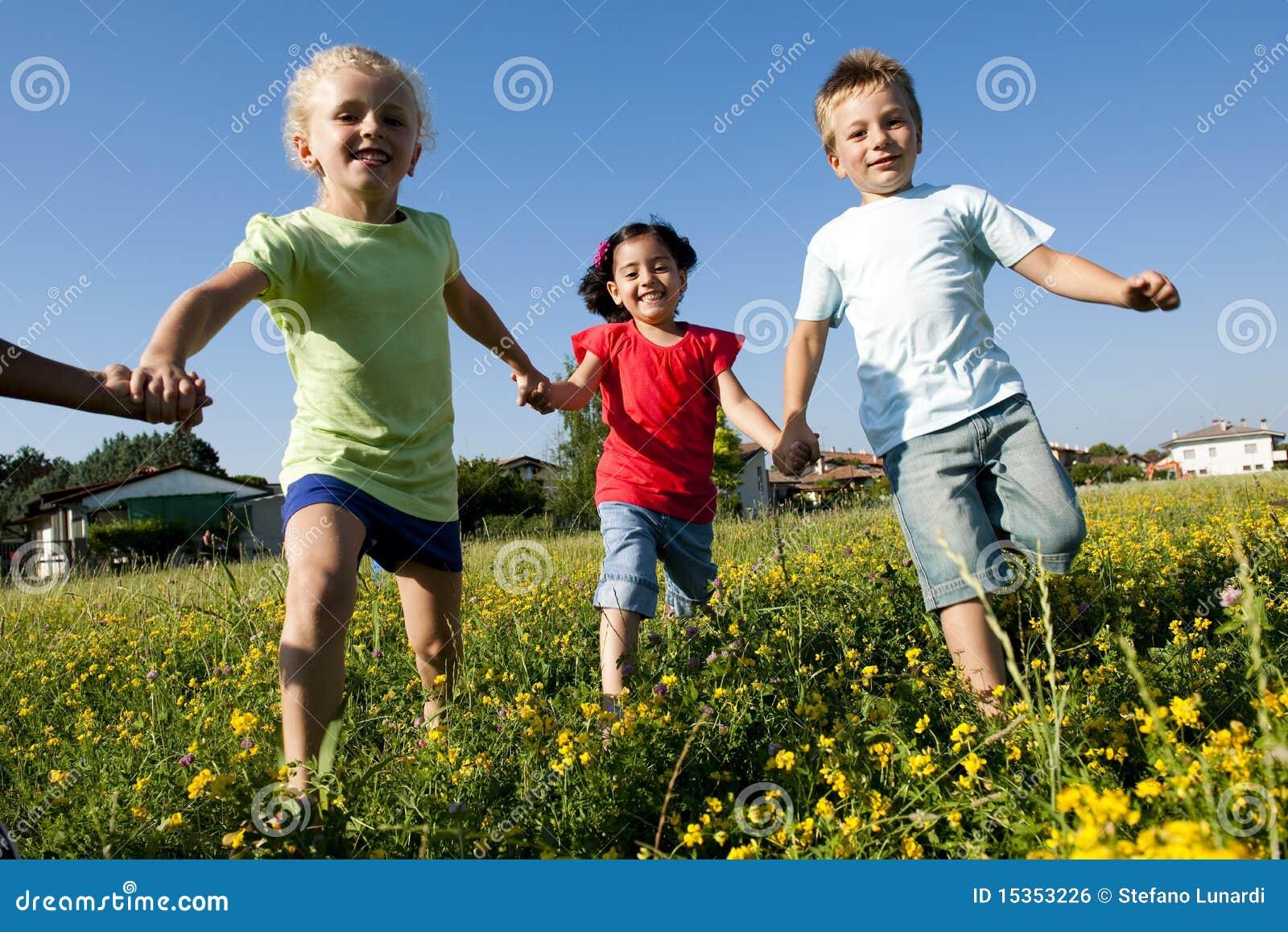 Tres niños que funcionan con las manos de la explotación agrícola