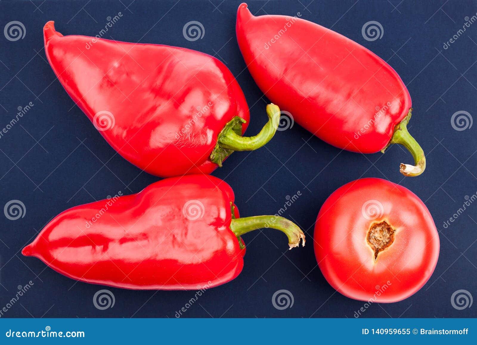 Tres paprikas rojos grandes brillantes y un tomatoe rojo en el primer azul de la opinión superior del fondo
