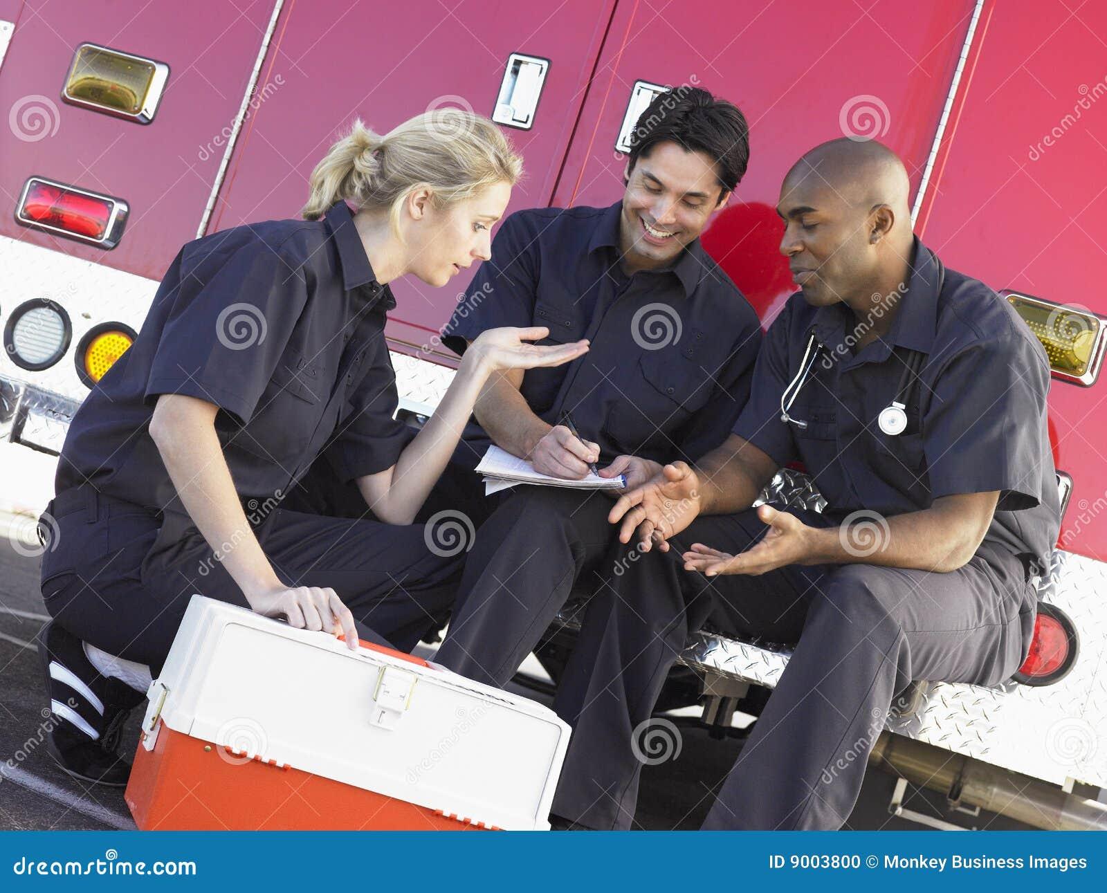 Tres paramédicos que charlan en ambulancia