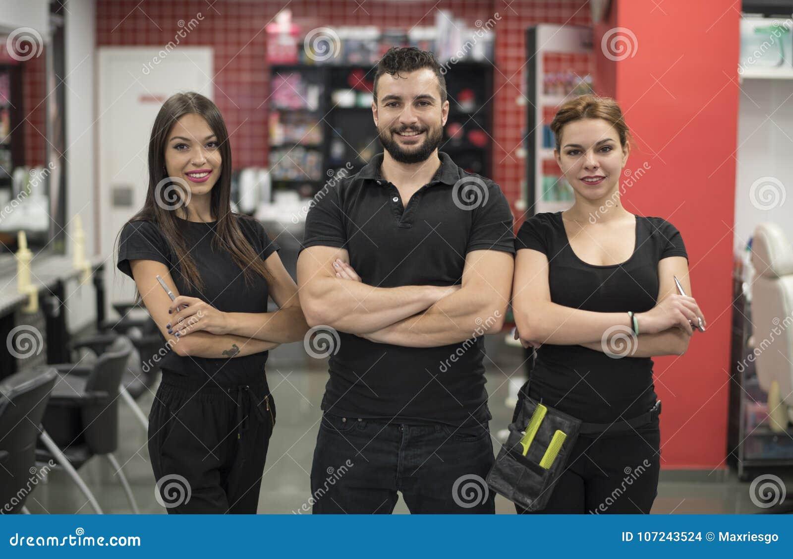 Tres peluqueros que presentan en peluquería de caballeros