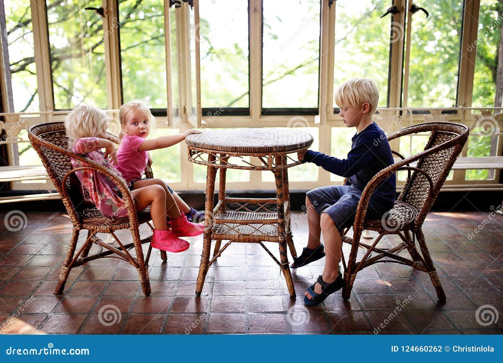 Tres pequeños niños que se sientan en una tabla vieja de los bistros en un Sunroo