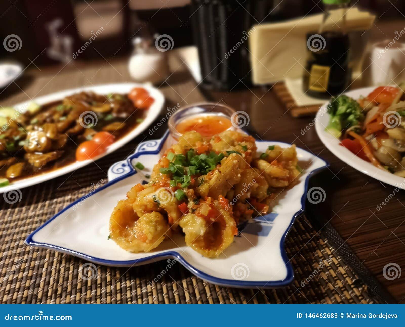 Tres platos orientales con carne de vaca, camarones, tomates, las zanahorias, la pimienta roja y los tallarines de arroz